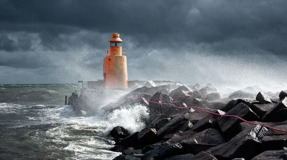 orange lighthouse on rock