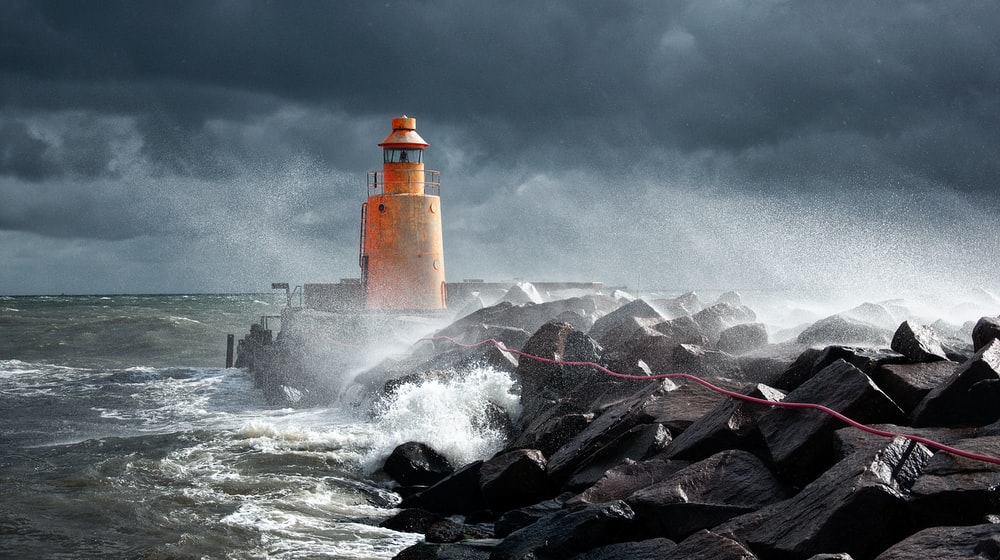orange lighthouse on rock