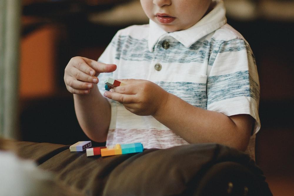 boy holding block toy