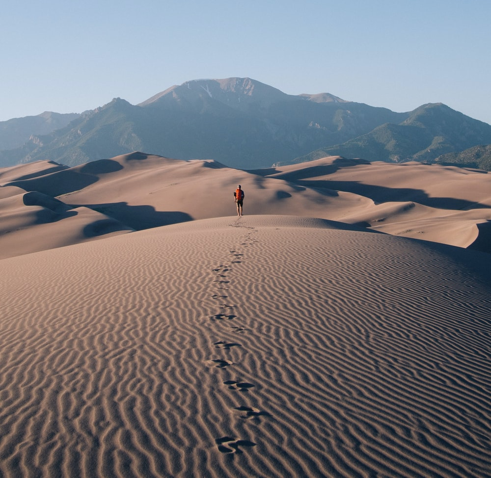 person walking on sand dunes leaving footprint trails behind