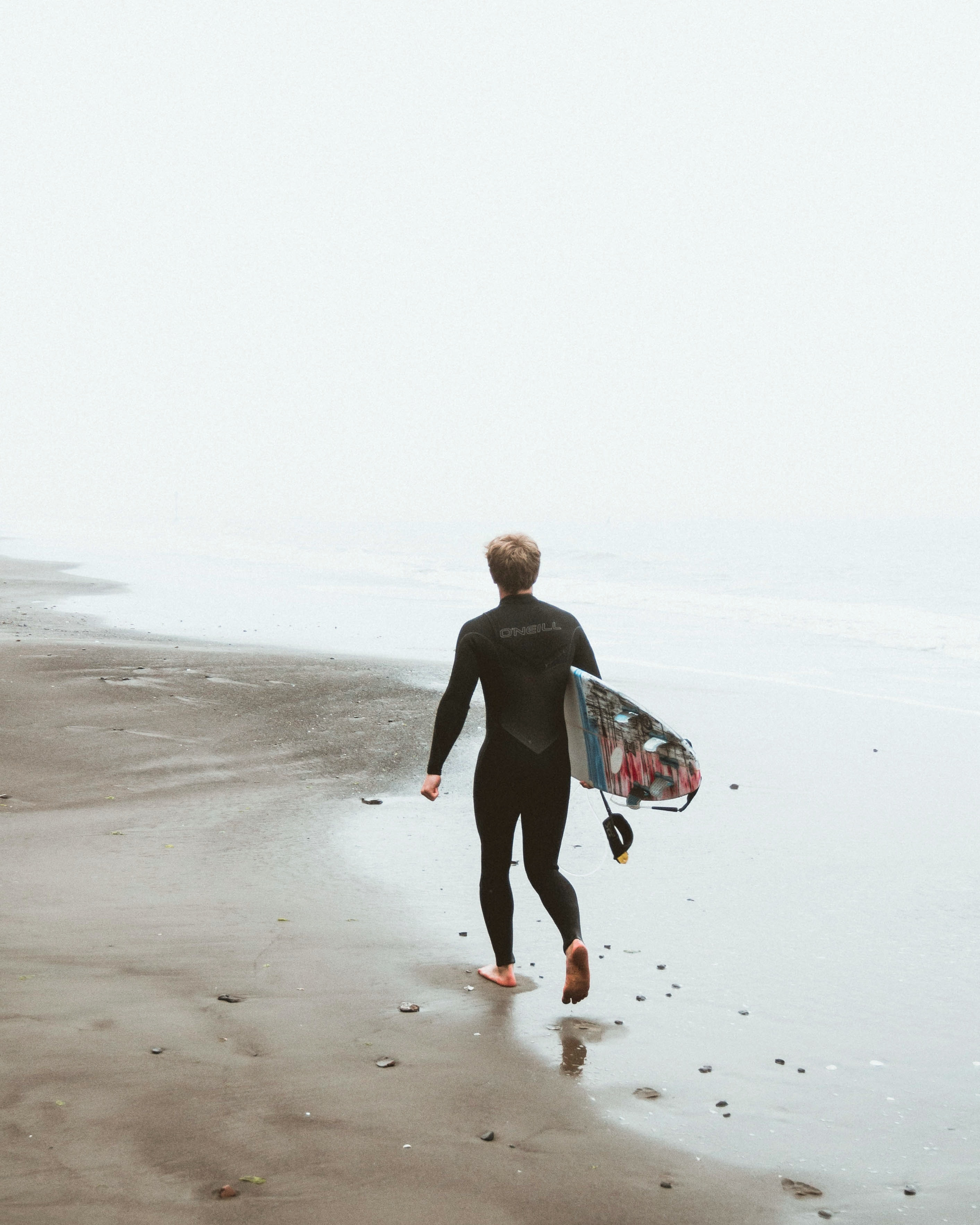 Surfer walks along a misty seashore on the ocean