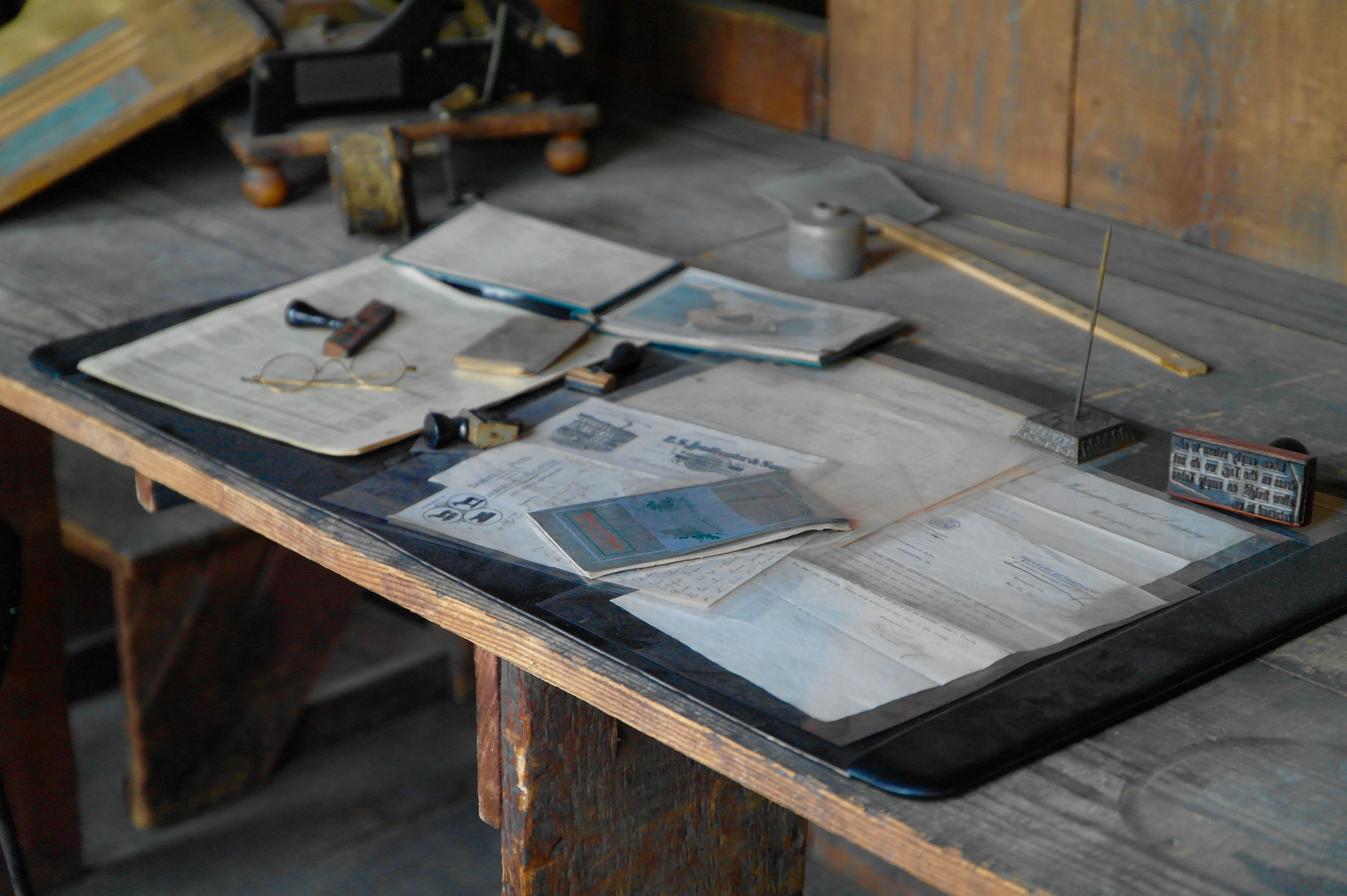 Documents and maps on a messy workbench