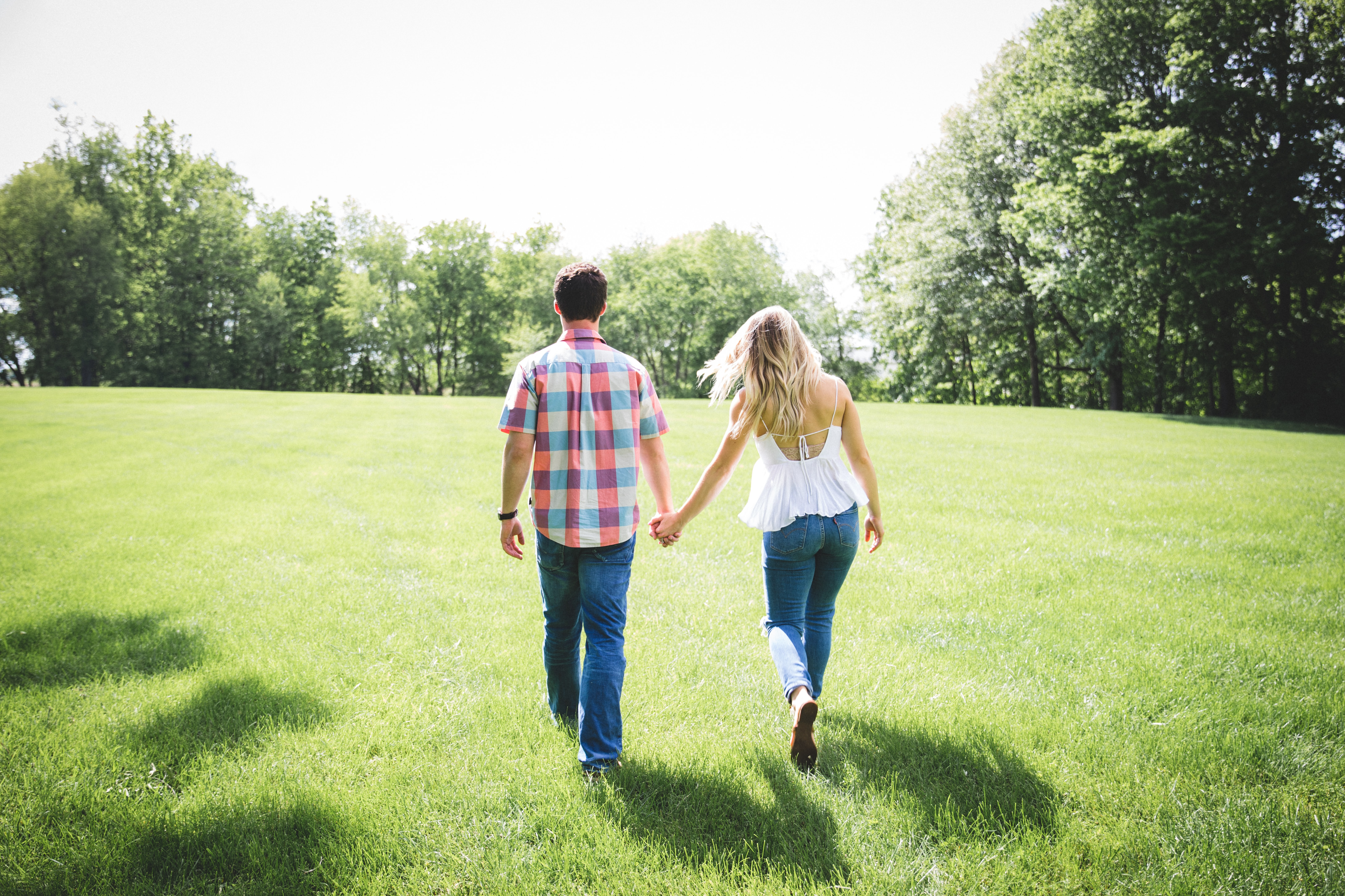 The back view of a couple holding hands walking in a park.