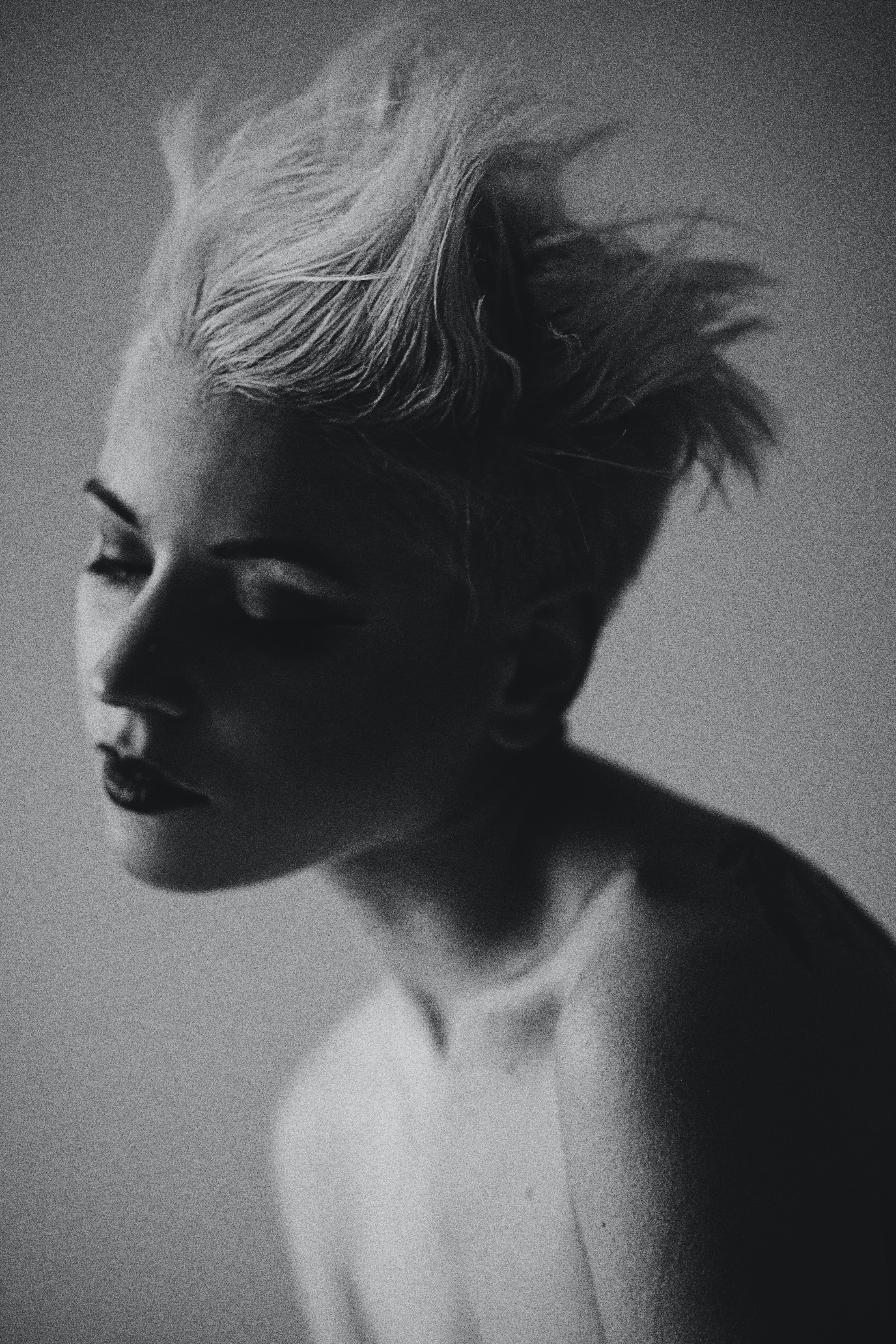 Black and white shot shot of shirtless woman with short blonde spiked hair