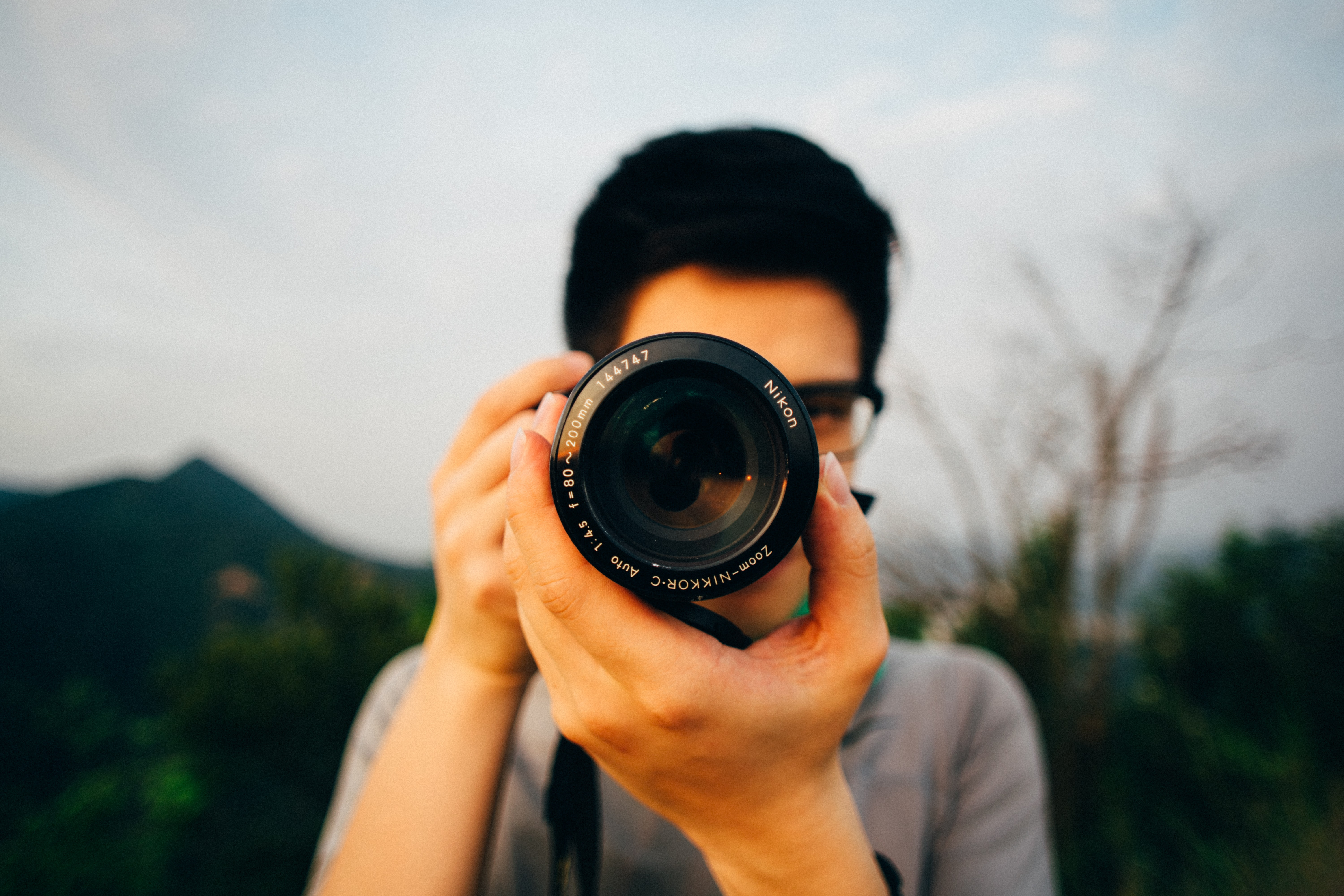 Macro of a man with glasses focusing a camera lens at the viewer in front of an outdoor scene