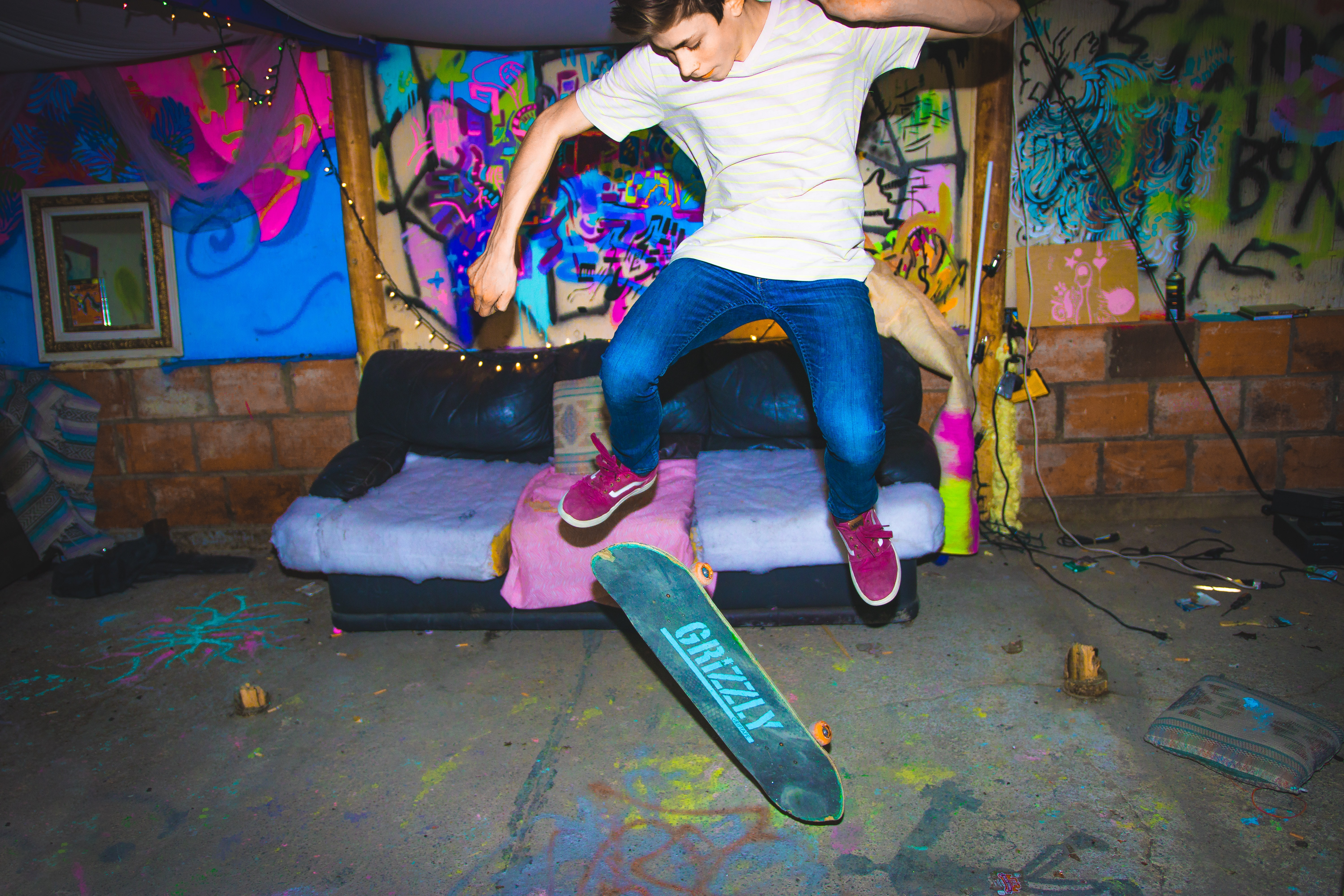 A skateboarder does a trick in front of a couch and neon graffitied wall