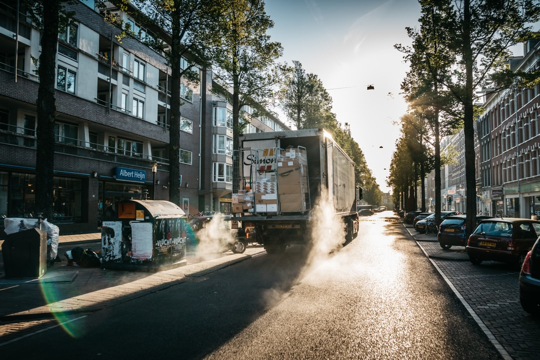 truck moving on gray concrete road between trees