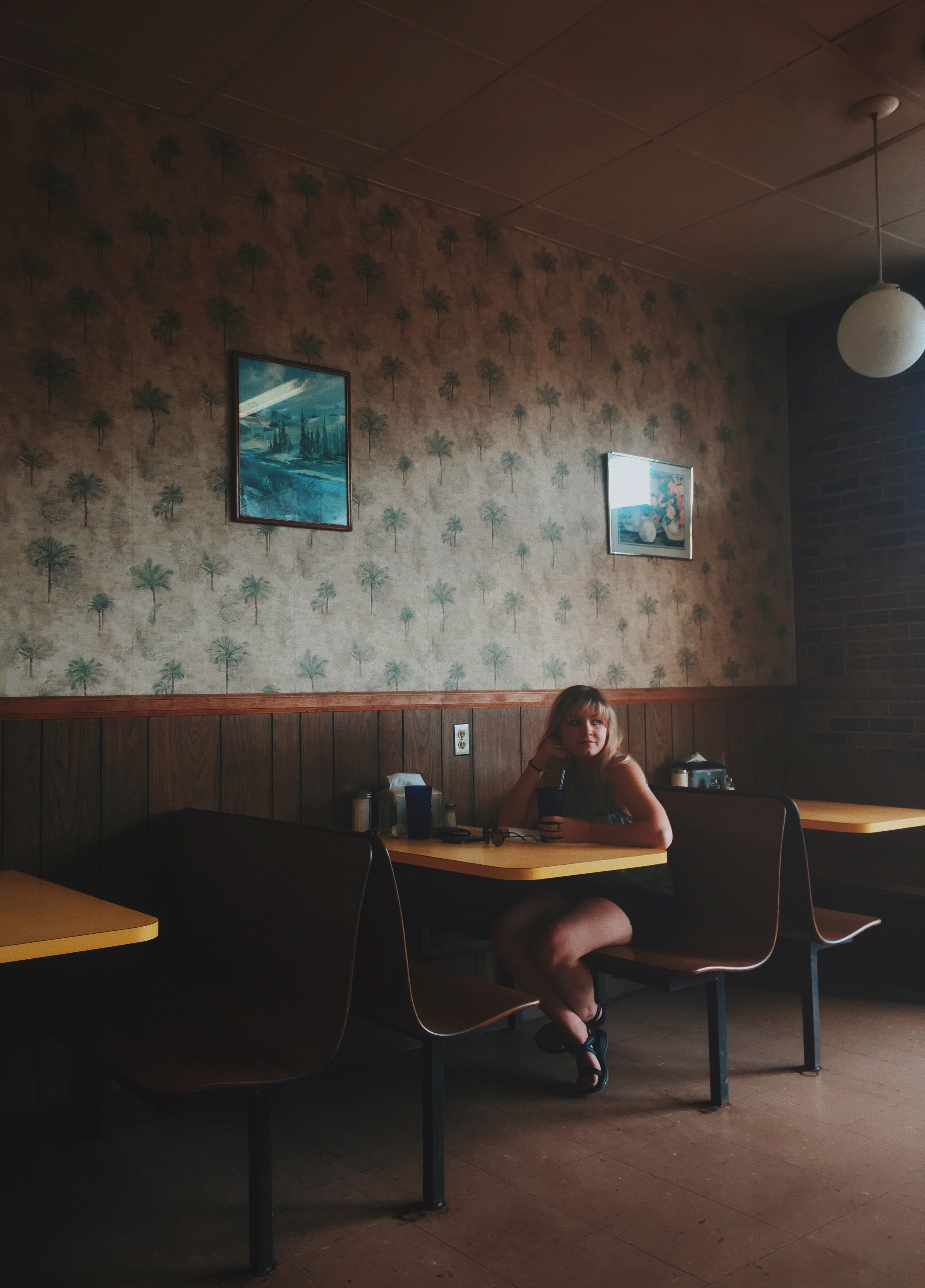 A lone woman sitting at a table in a cozy café