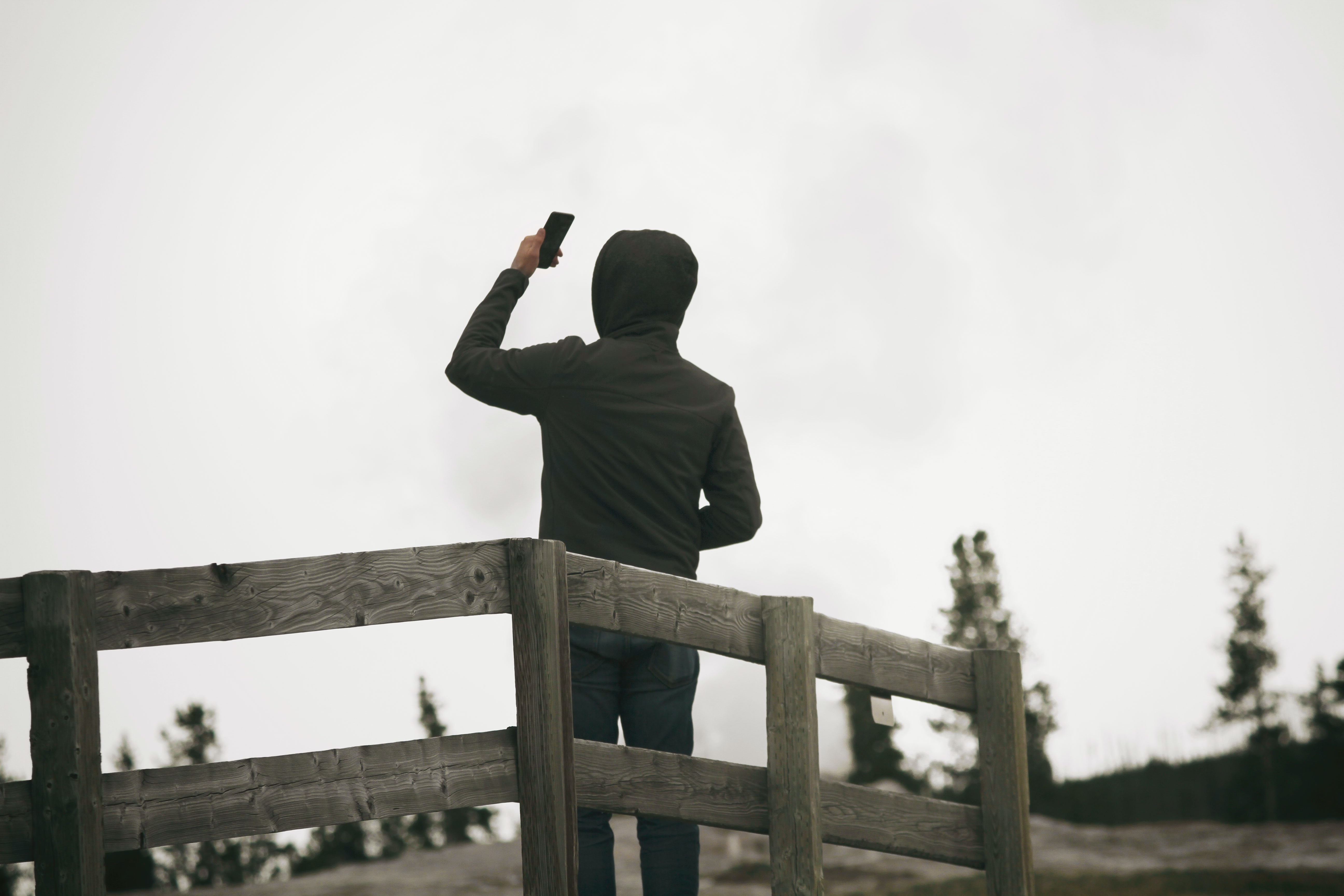 A man in a hoodie faces away by a wooden fence, taking a selfie