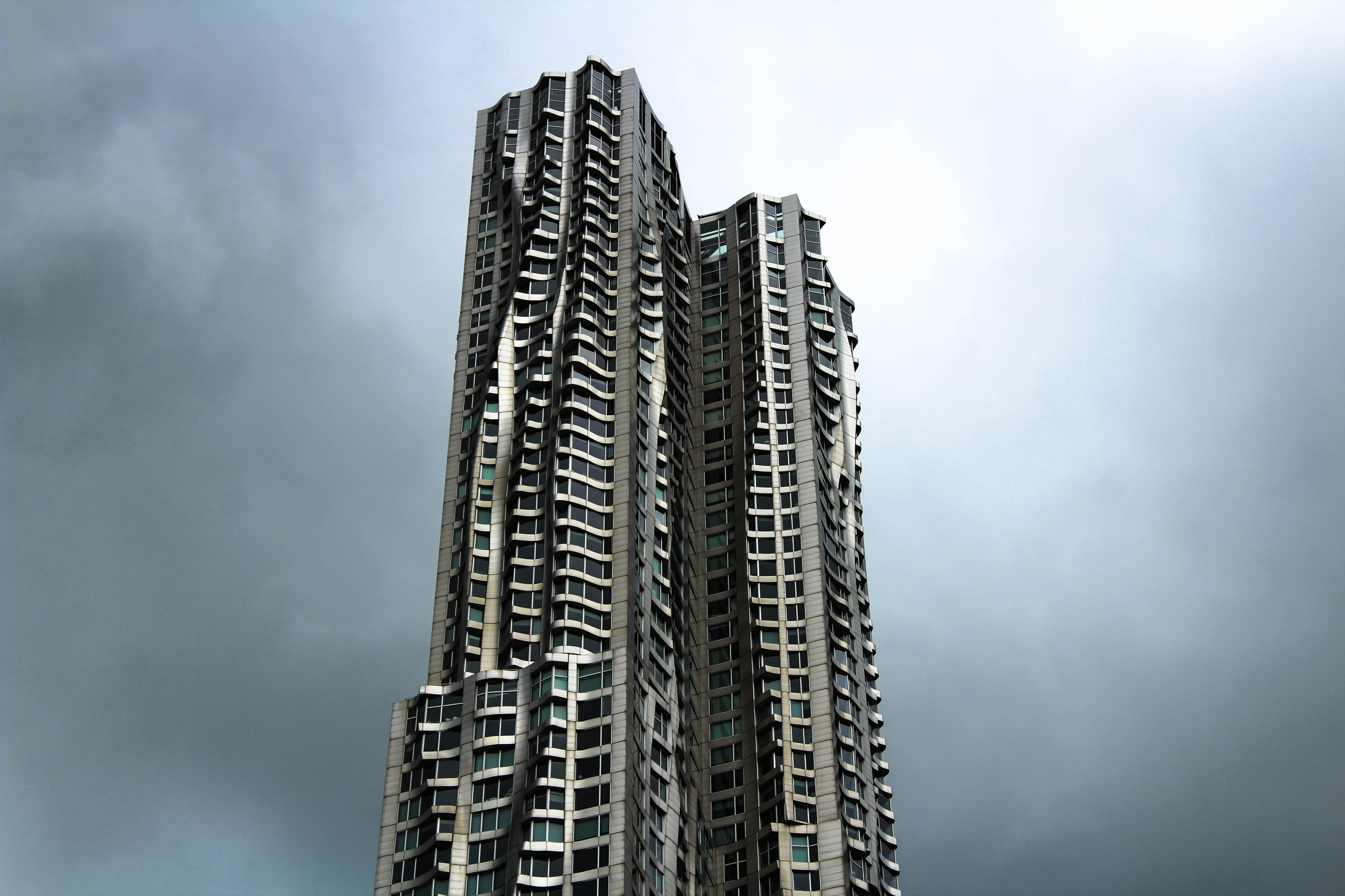 Twin skyscrapers with undulating curved facade rise against the gray sky.
