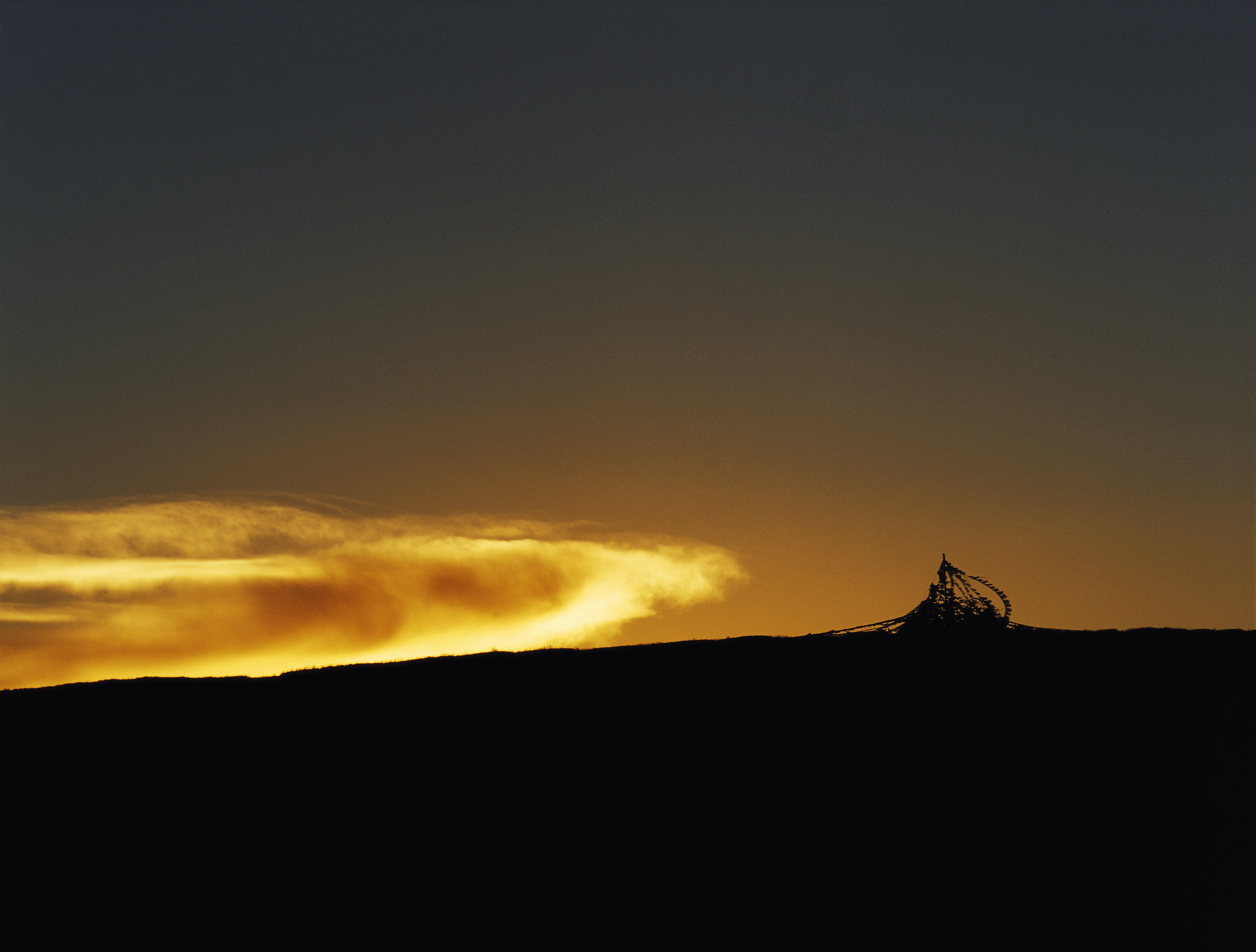 Deep gold sunset against a hill silhouette with glowing clouds.