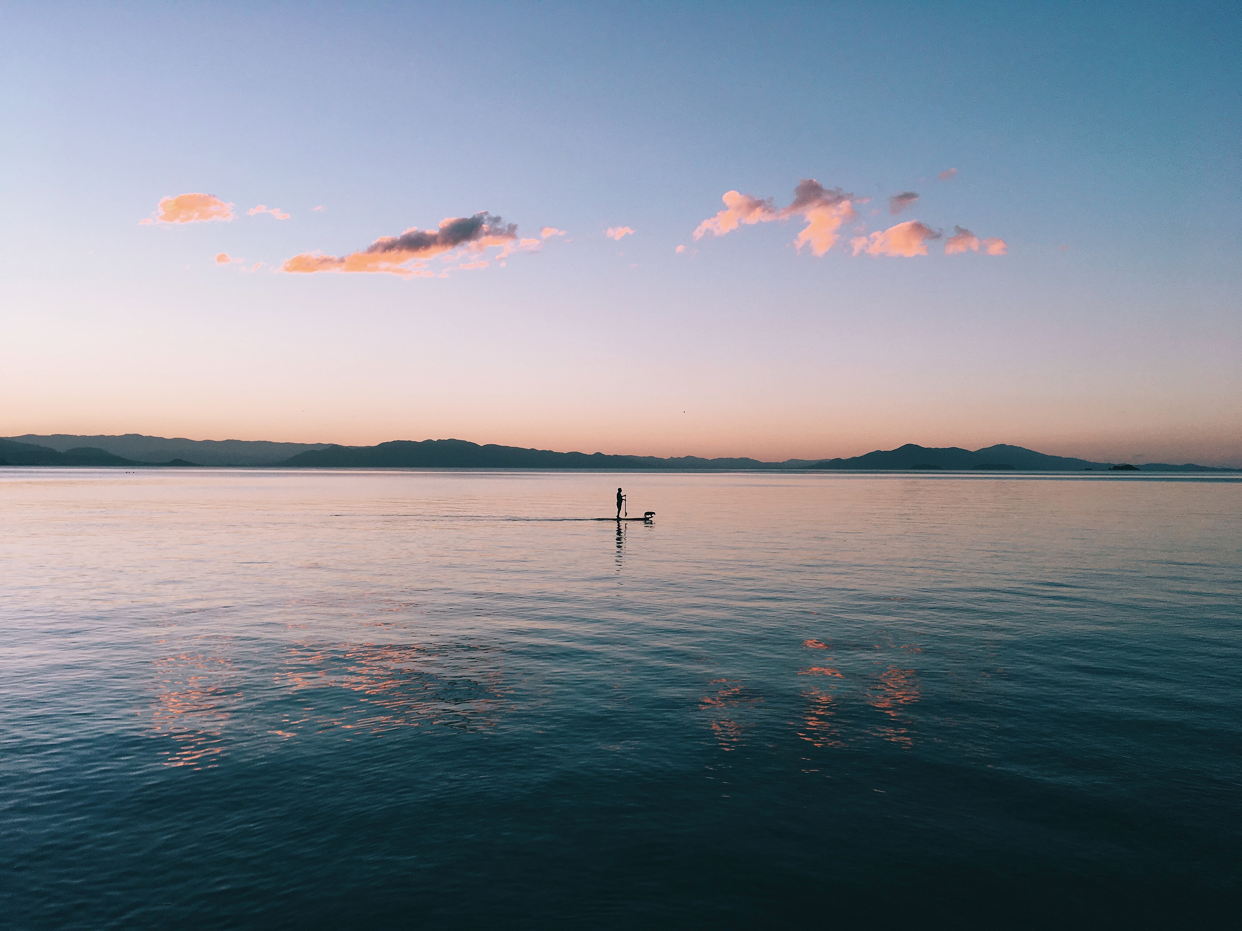 A person and paddle board on the water with a hilly horizon during dawn-or-dusk and a clear blue sky except for a small cluster of cloud
