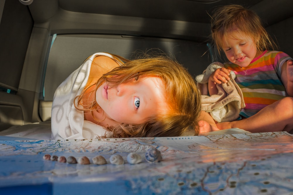 girl lying near gray seashells