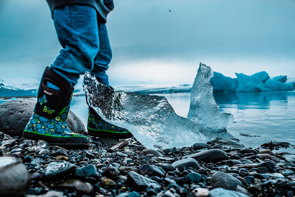 person standing on rocks beside iceberg and sea during daytime