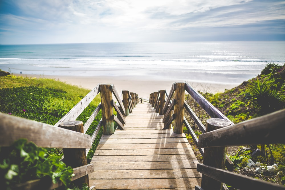 brown wooden walkway near beach during daytime