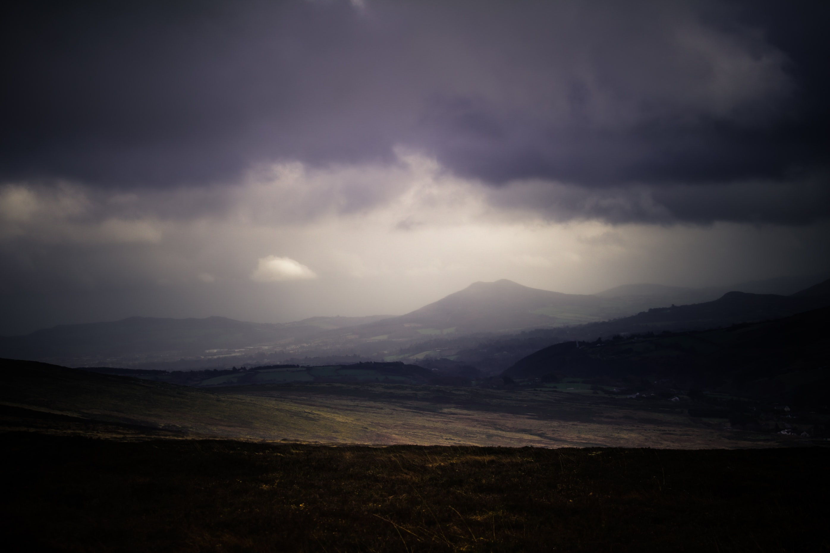 A dim shot of plains stretching to the low mountains on the horizon under gray clouds