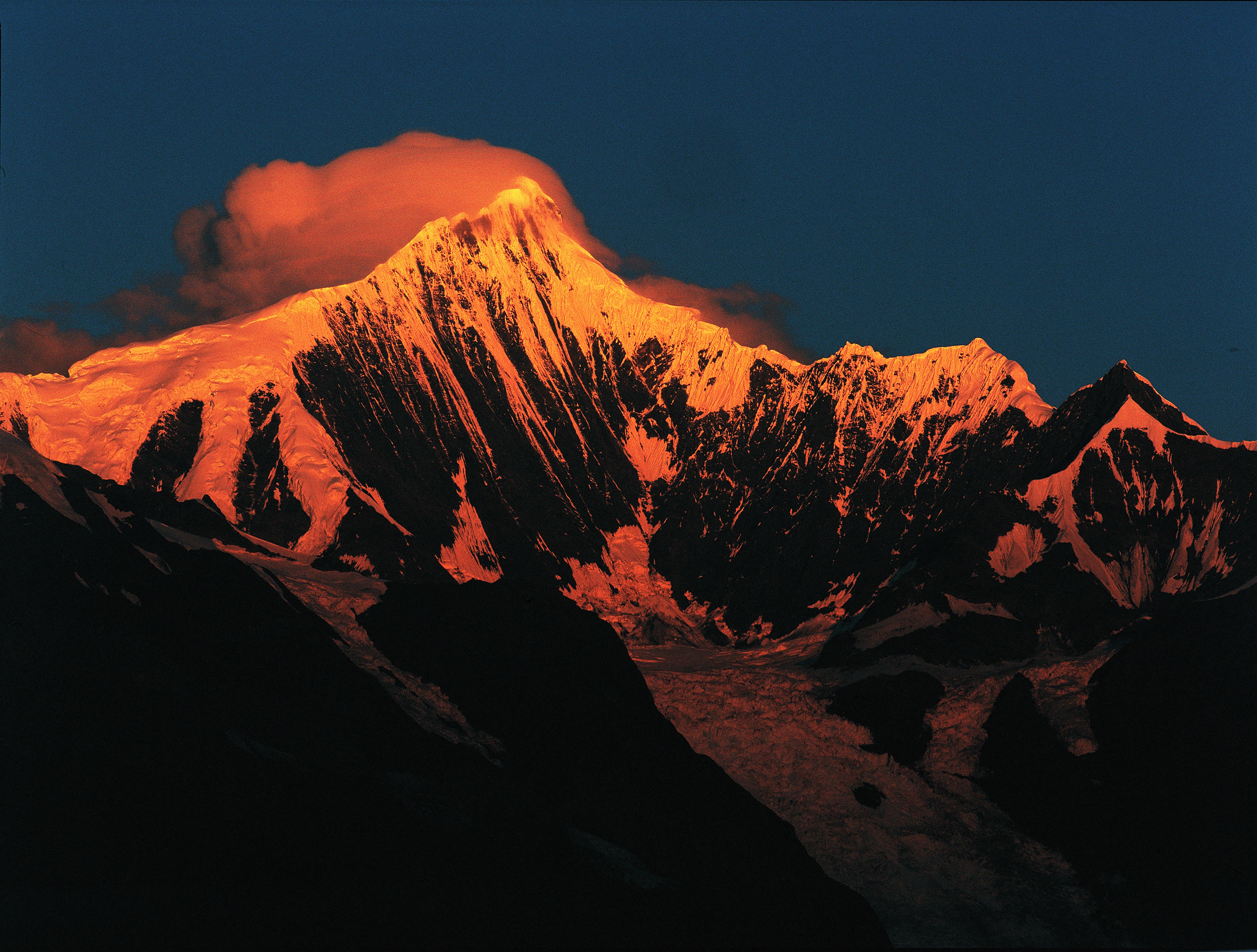 Orange sun rays illuminate a snow-capped mountain during sunrise