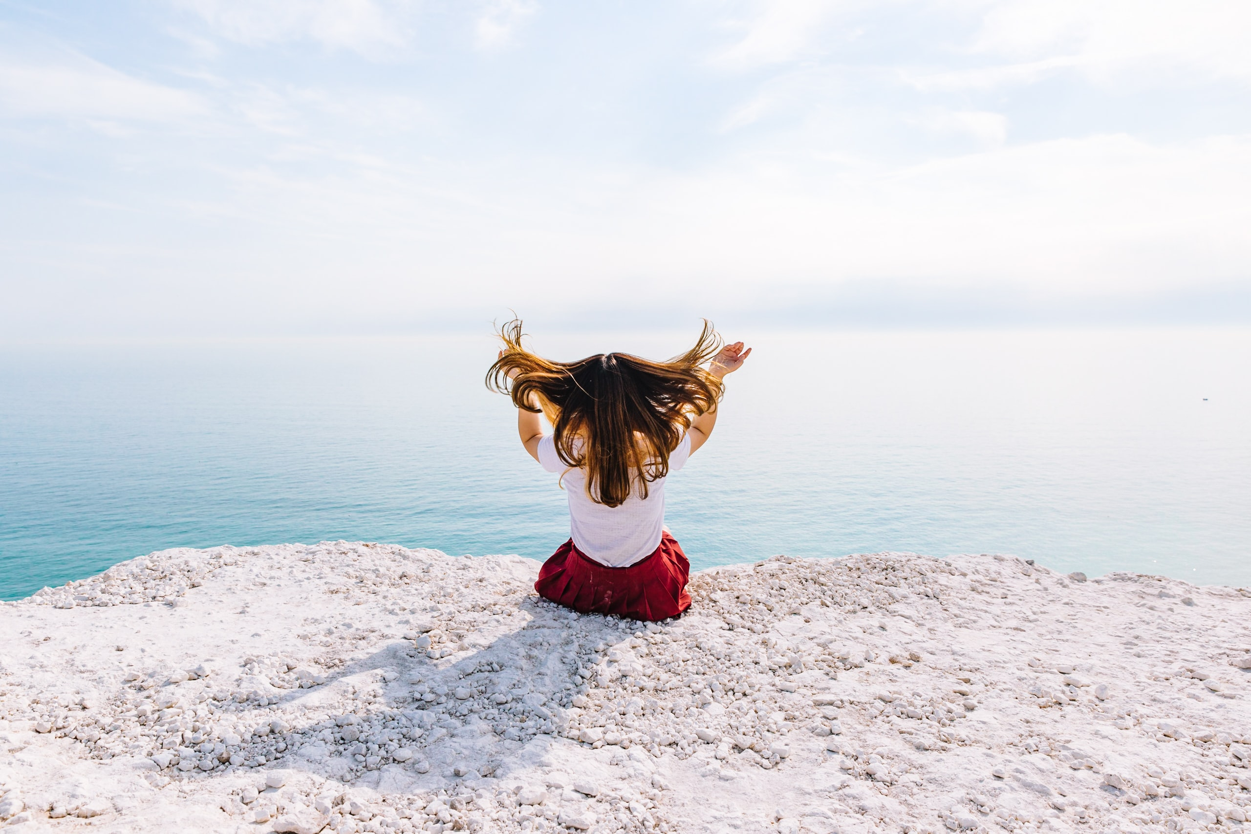 woman sitting on cliff near body of water