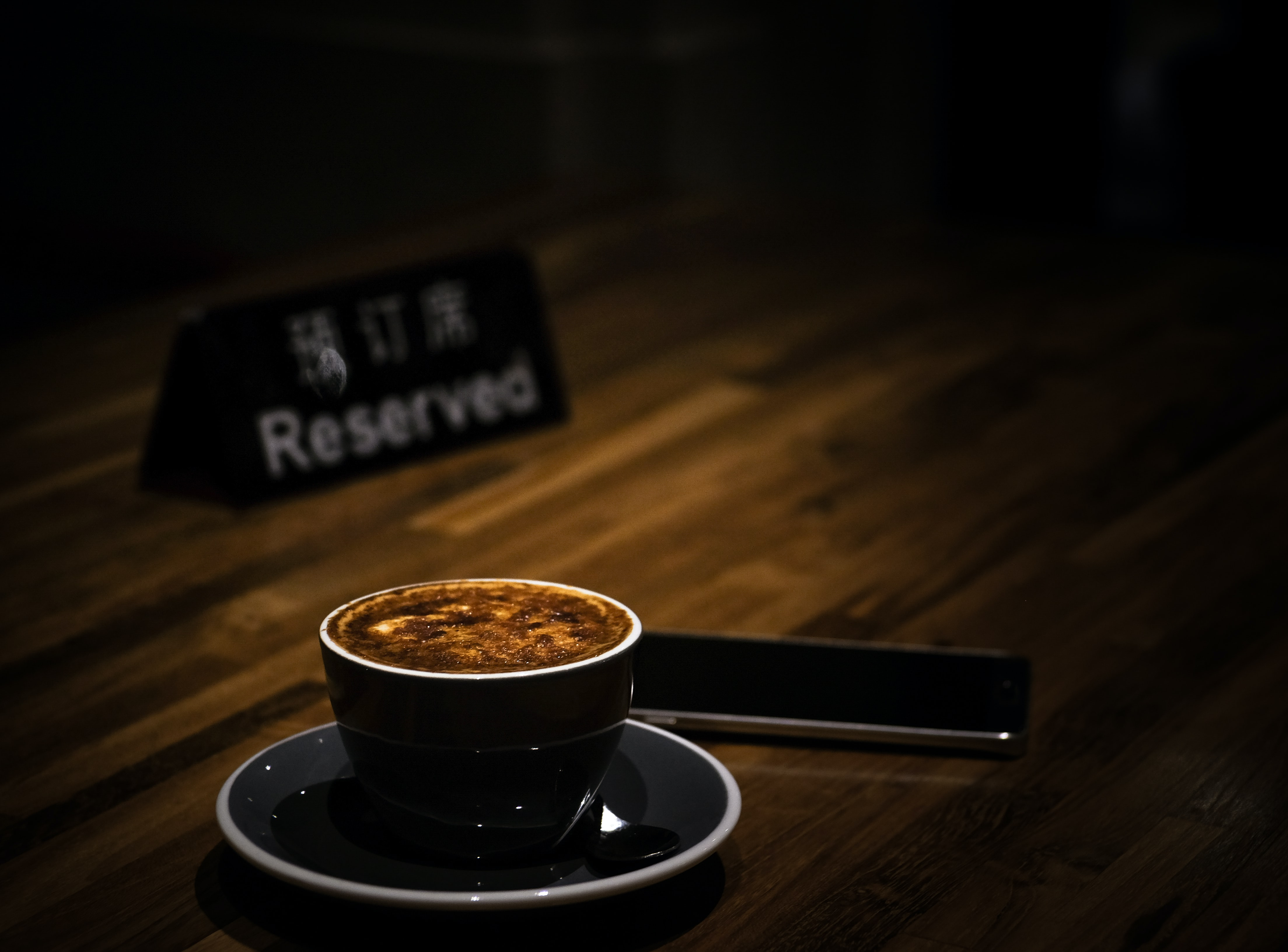 selective focus of teacup filled with coffee on reserved table