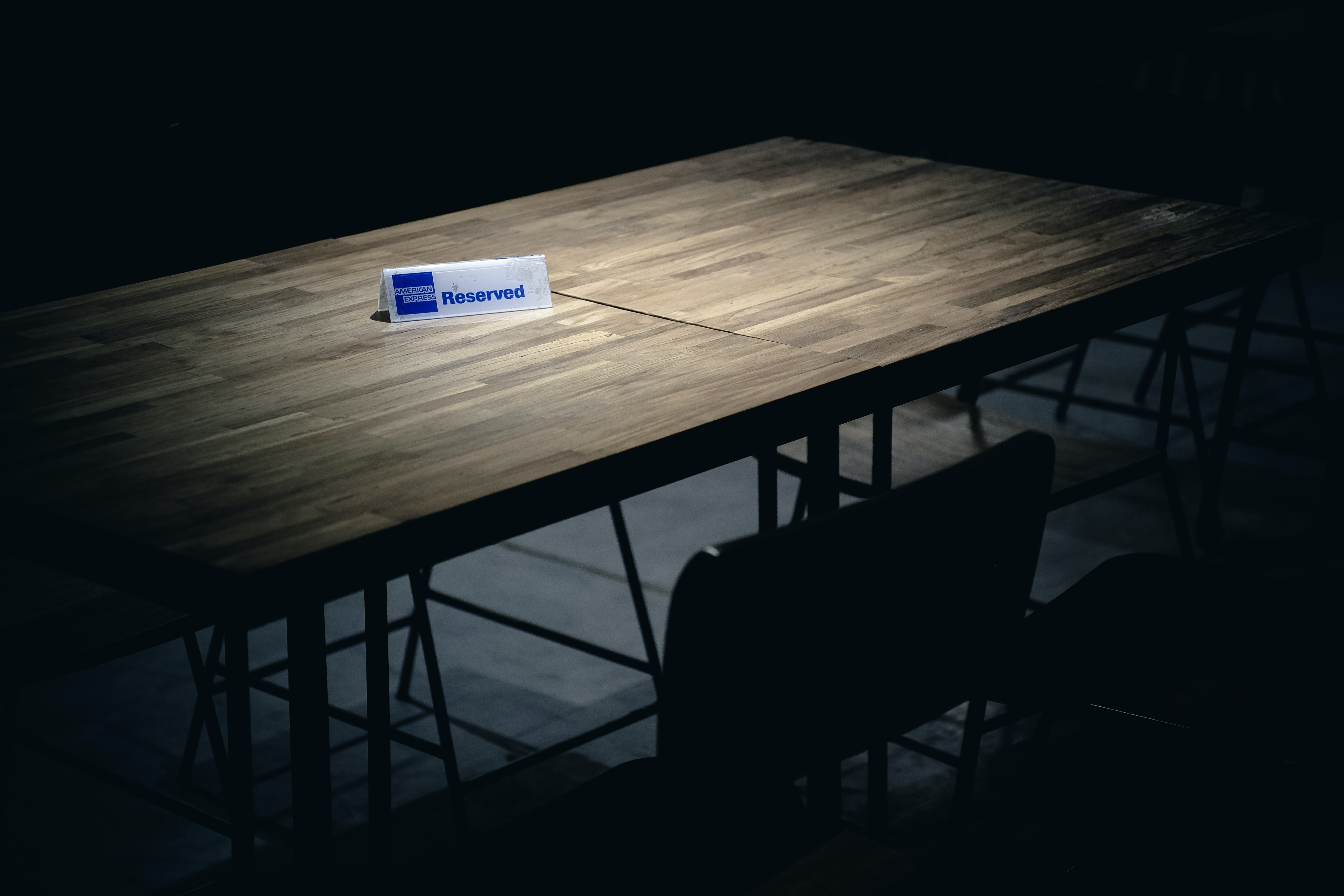 """An empty table shrouded in darkness is lit up with a spotlight on a table card that reads """"Reserved."""""""