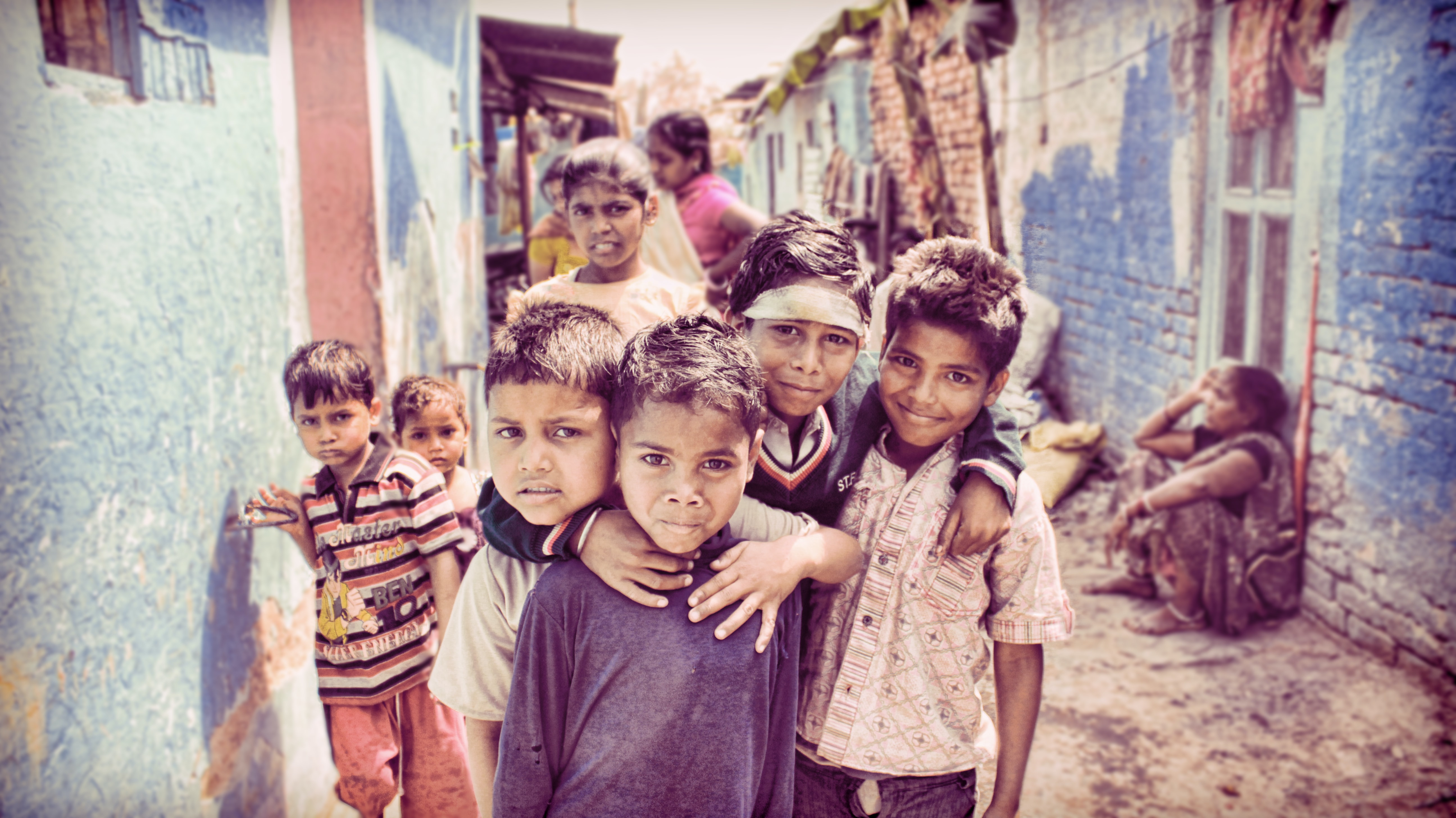 A group of smiling children in a dirt alleyway beside houses in India