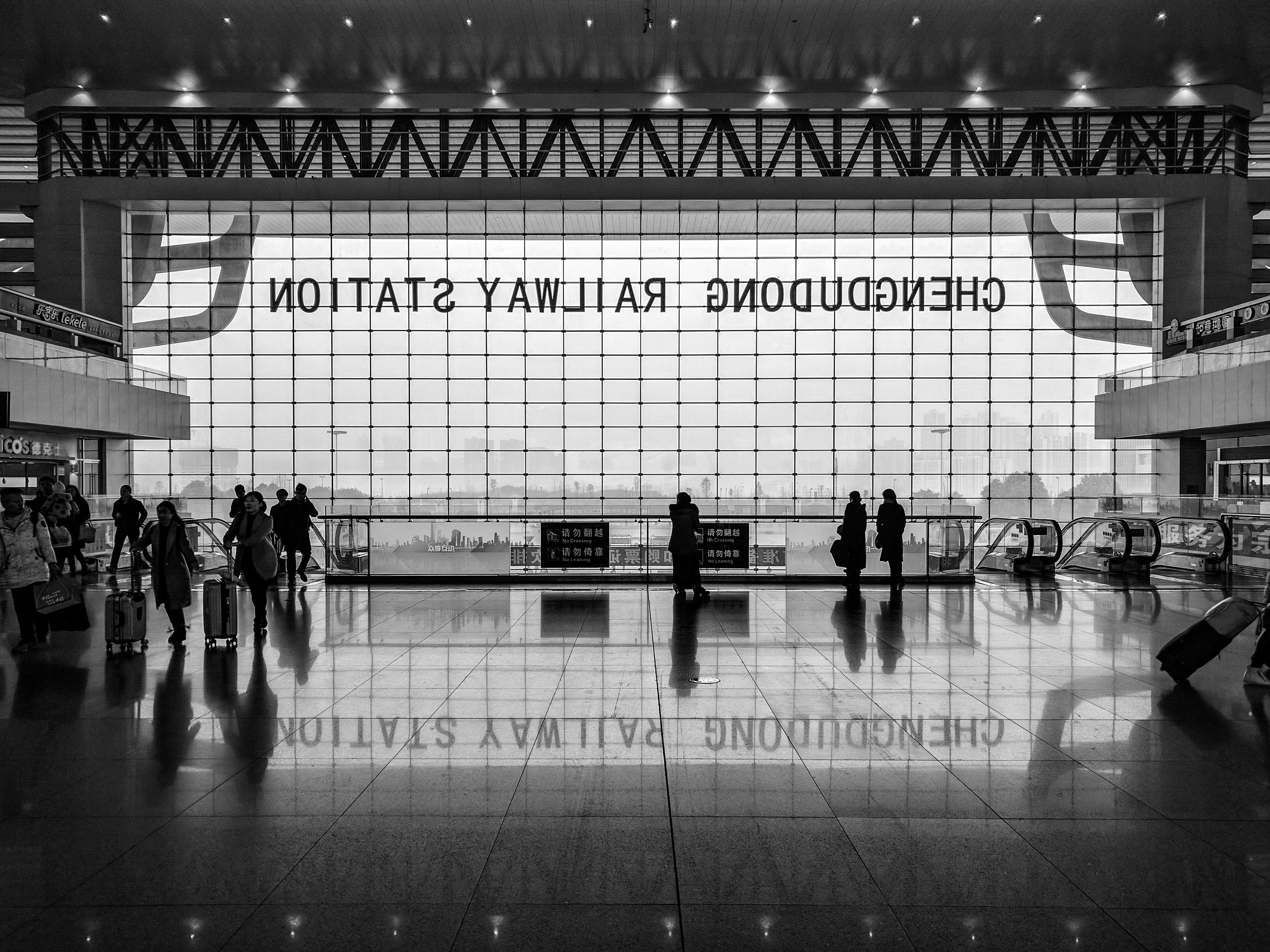 Black and white shot of station foyer with people and large window and reflection on floor