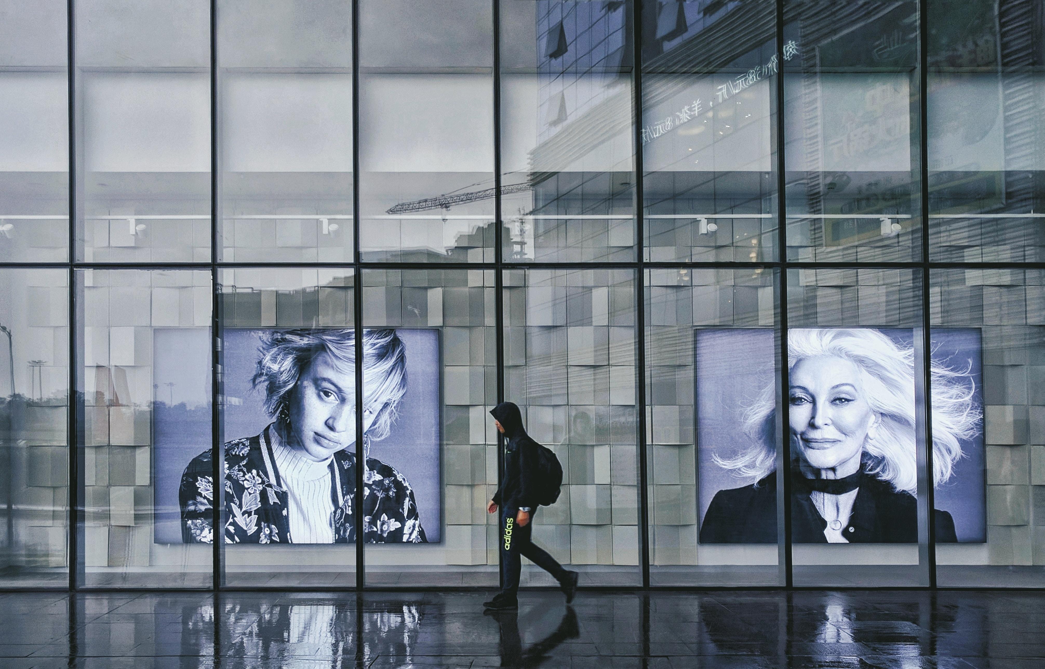 person wearing hoodie walking beside portrait of two women