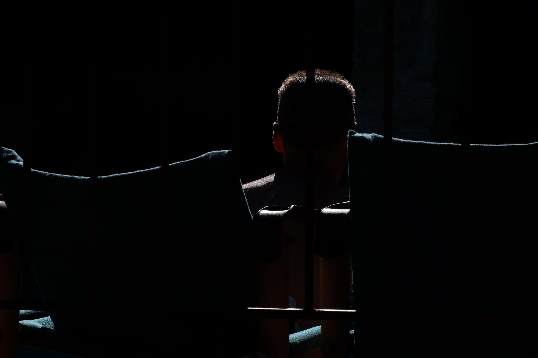 A dim shot of a silhouette of a man behind bars