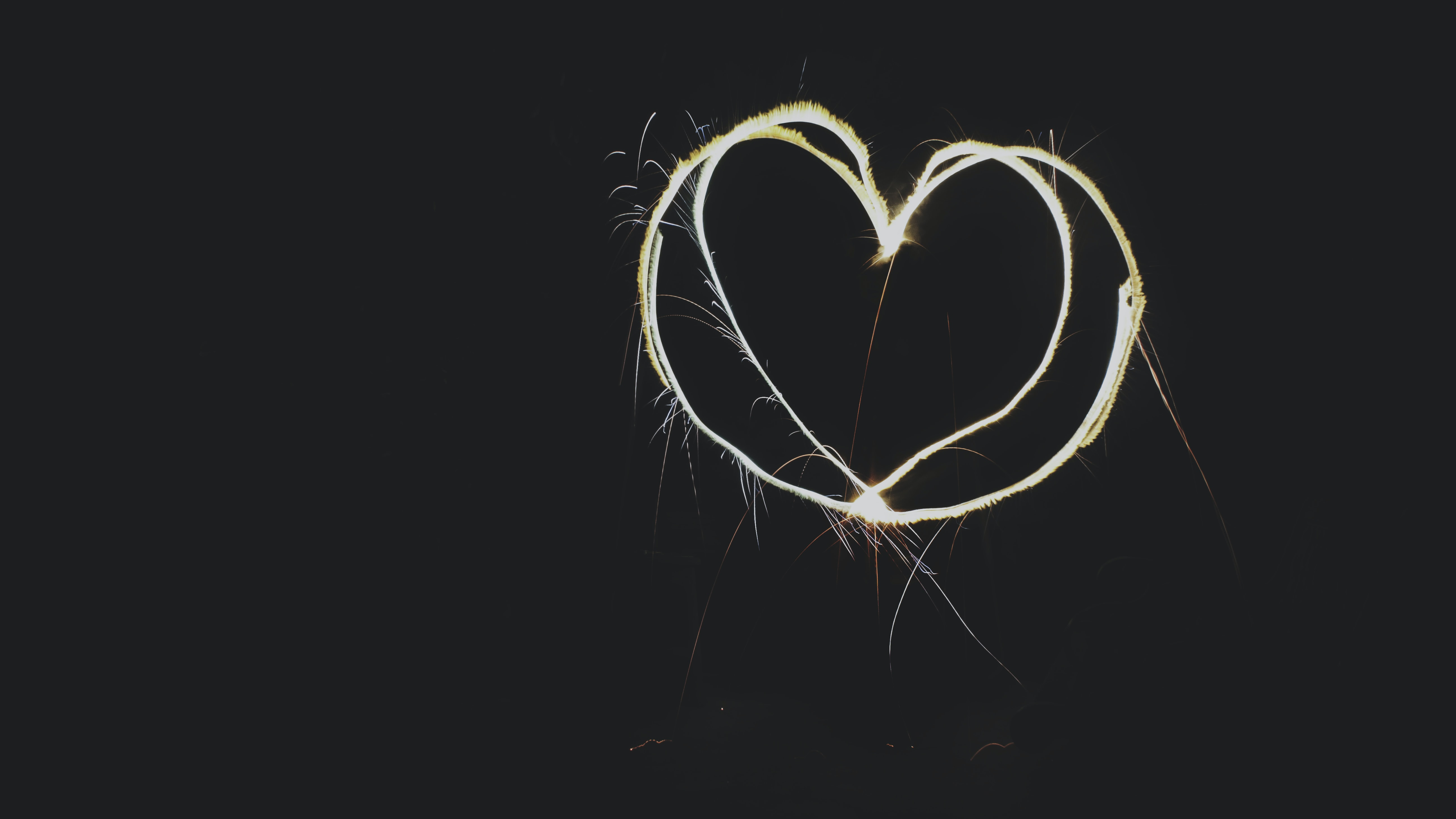 A heart-shaped sparkler against a black background