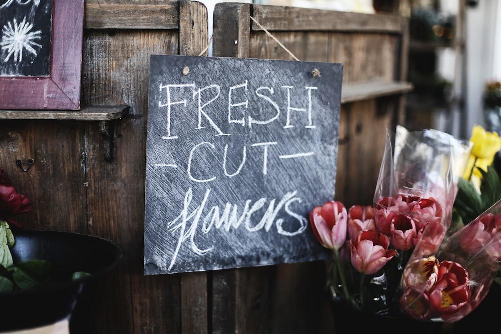 fresh cut flowers sign hanged on door beside flowers