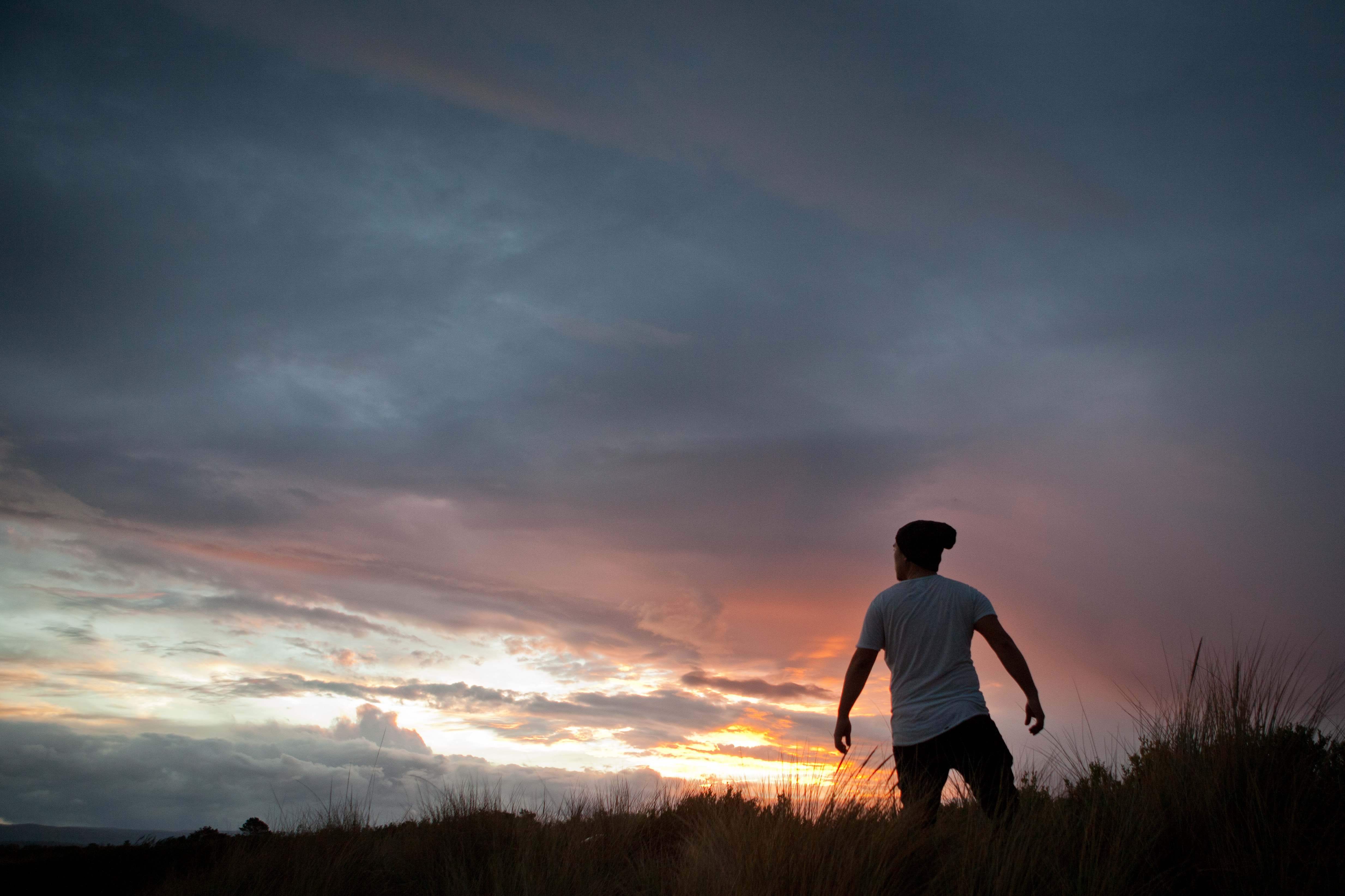 Man standing in a field, against an orange and light blue sunrise with grey clouds.