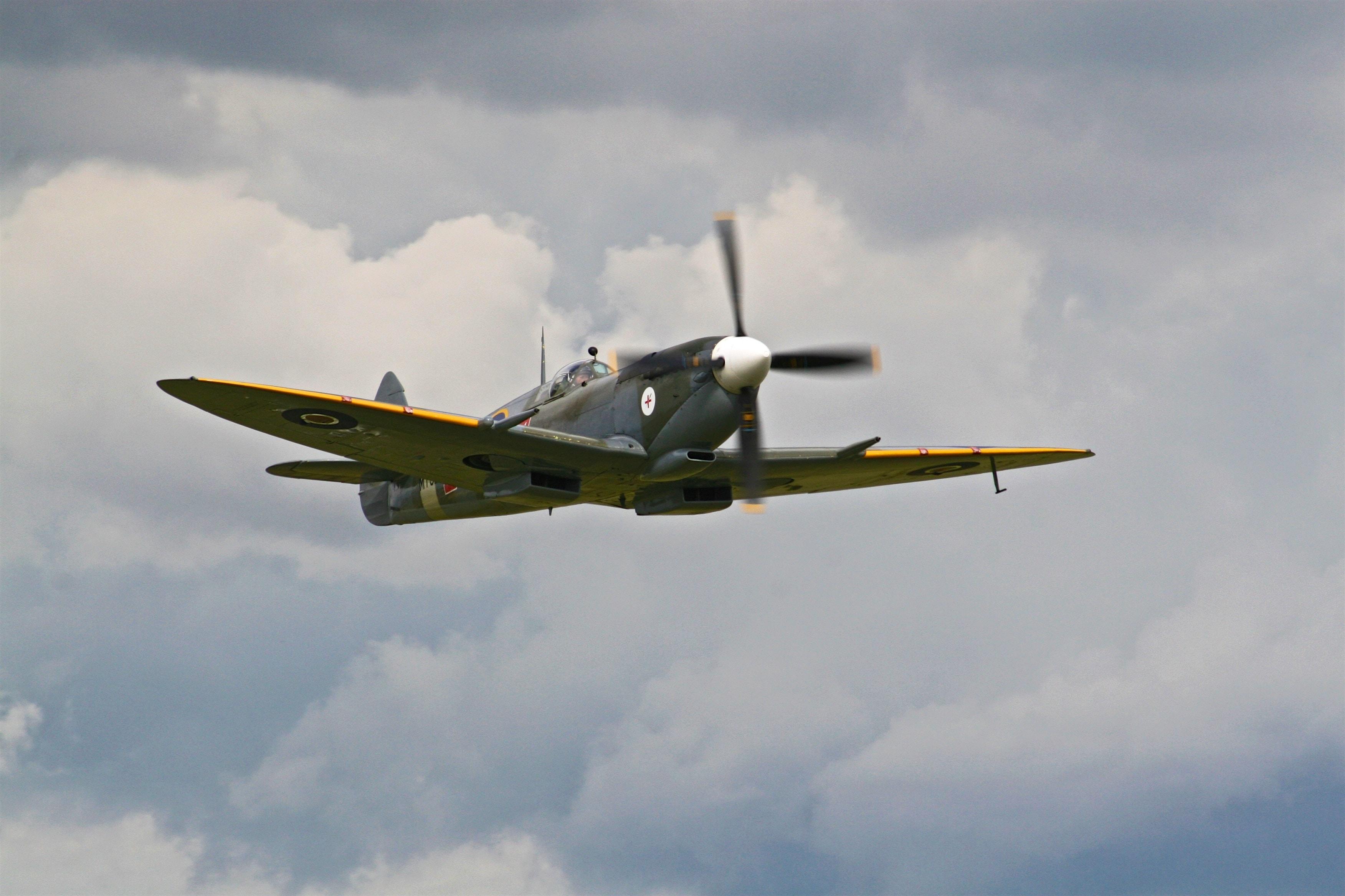 A vintage propeller plane flying in cloudy skies.