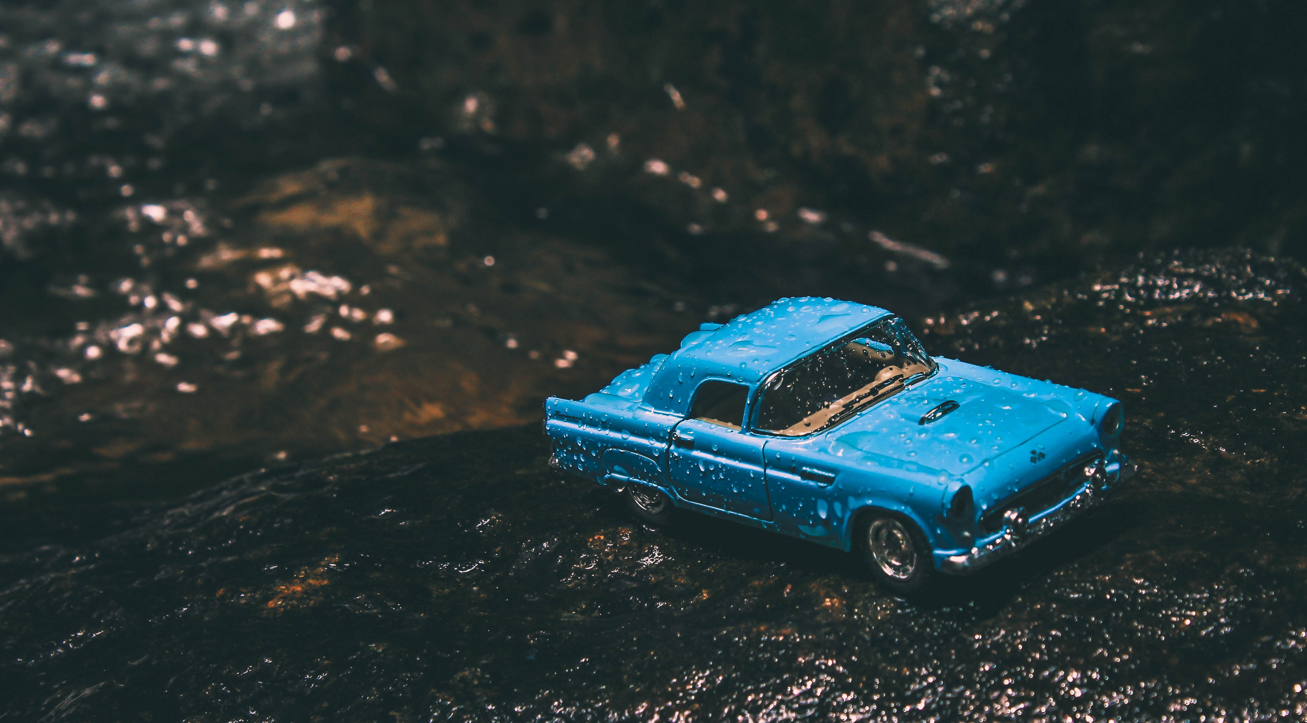 A blue toy car driving through the wet dirt on a forest ground