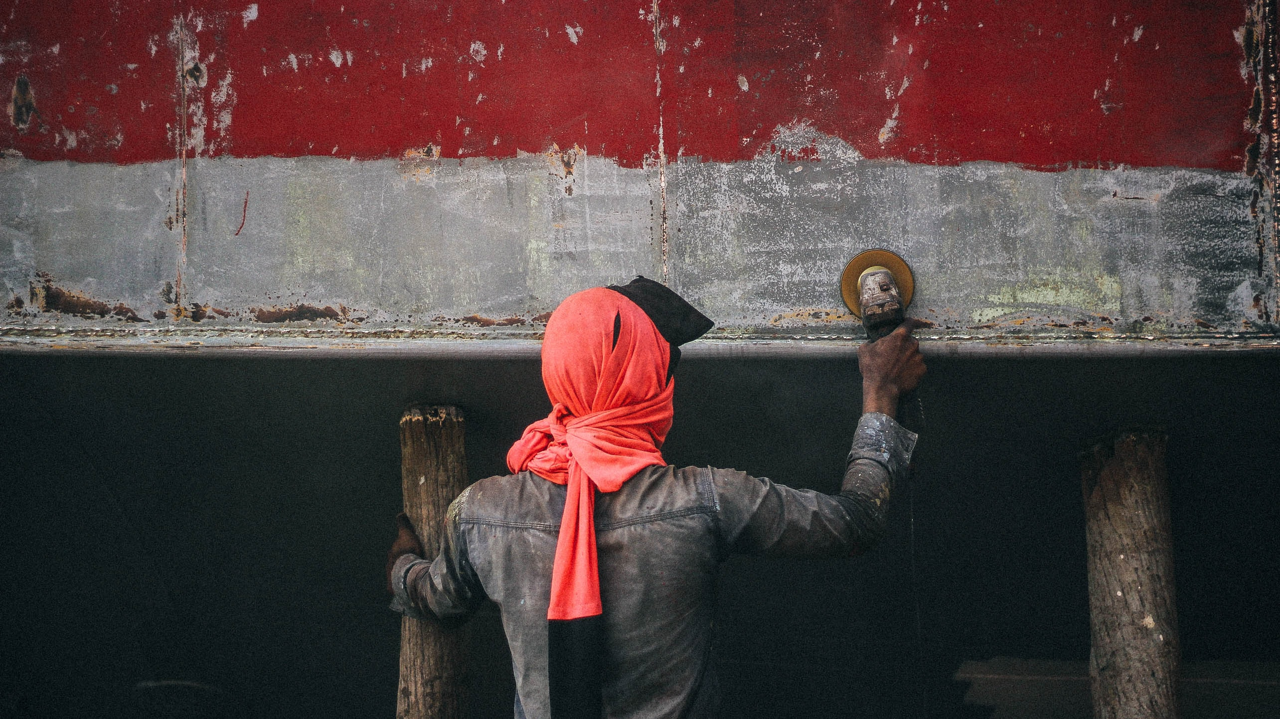 A person wearing a pink headscarf working on restoring a weathered boat