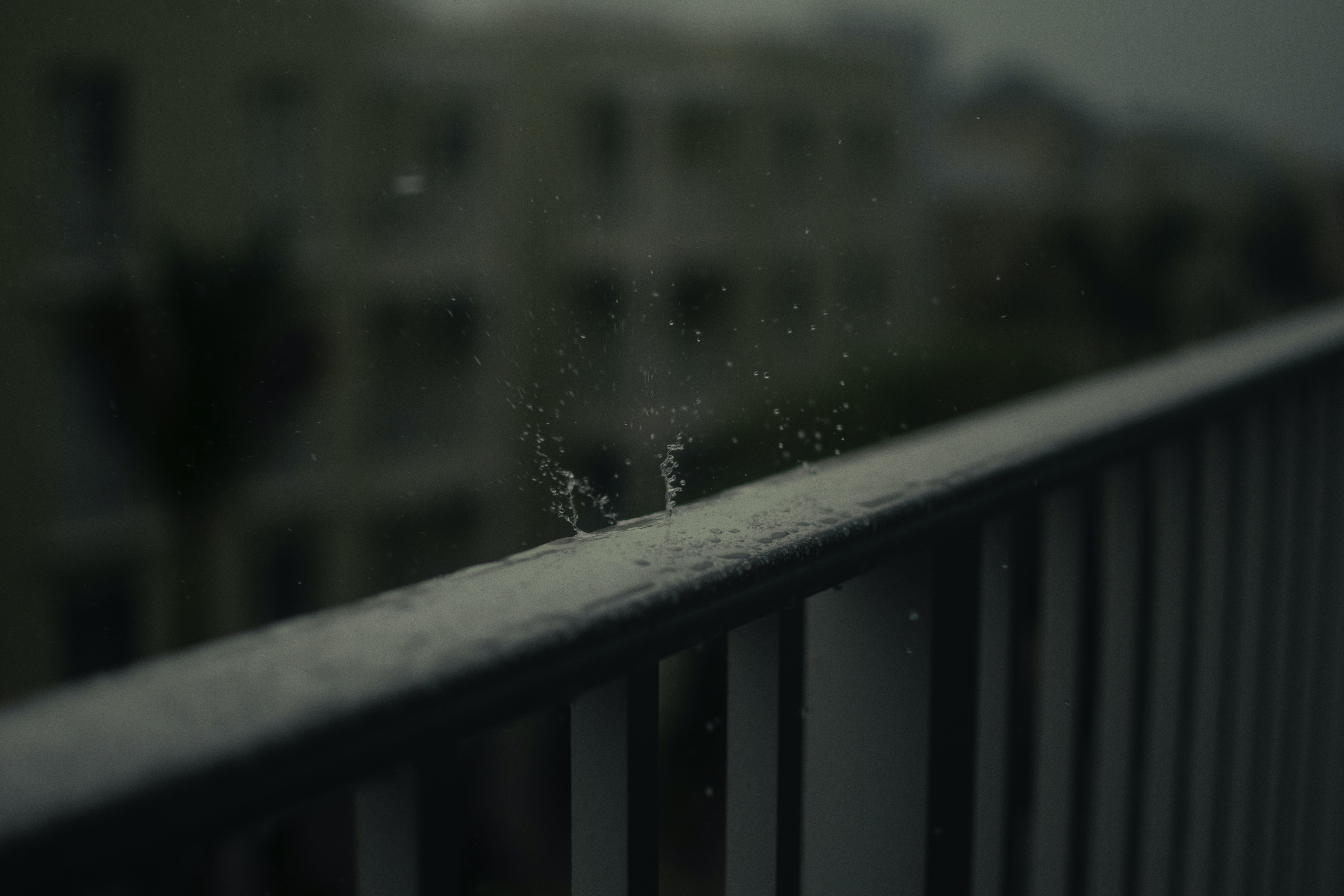 timelapse photo of water drop on black wooden fence