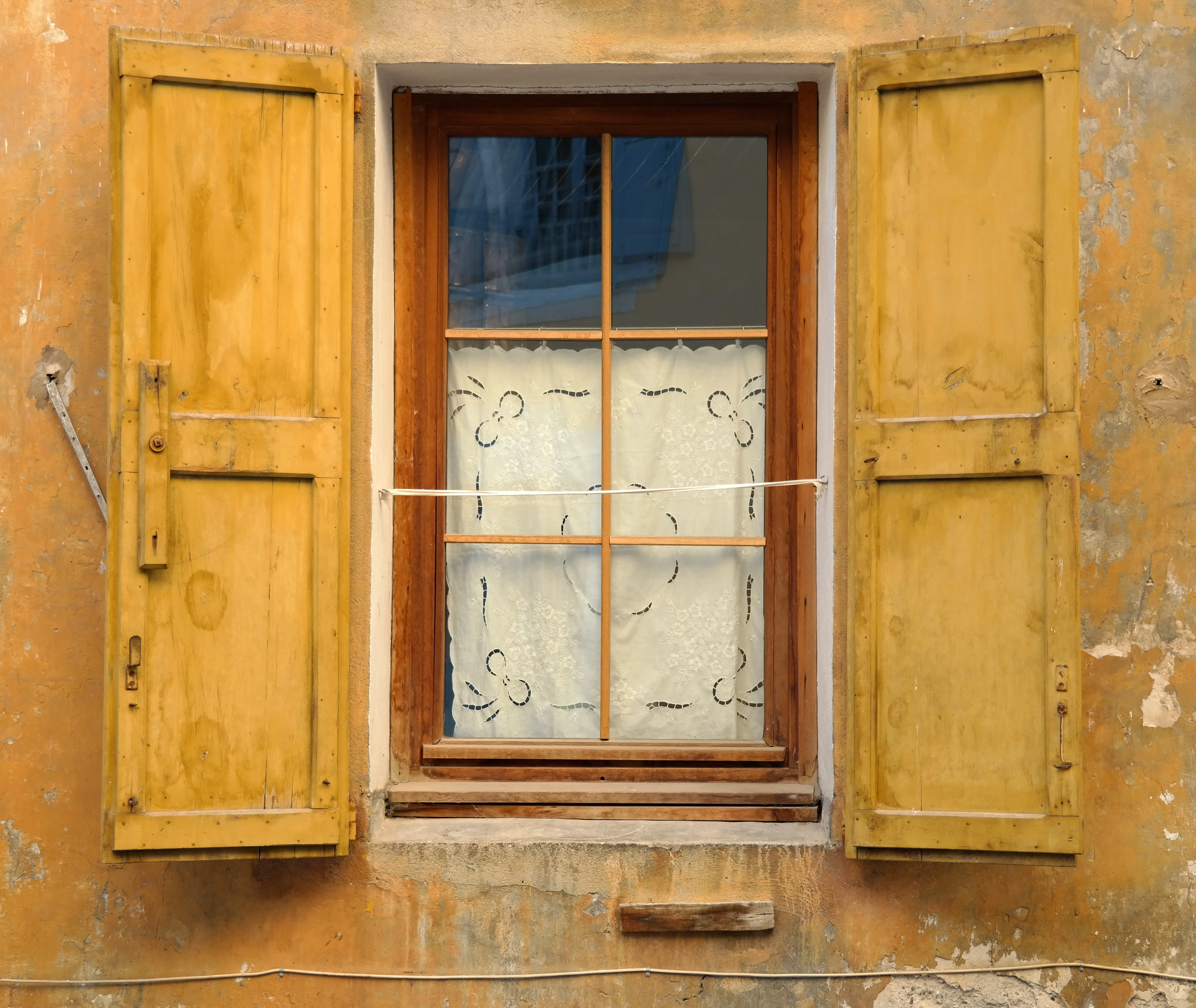 An open wooden glass window covered with a white sheet showing the reflection of another window of blue color.