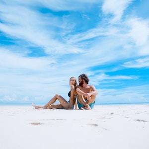 man sitting beside of woman in black bikini top