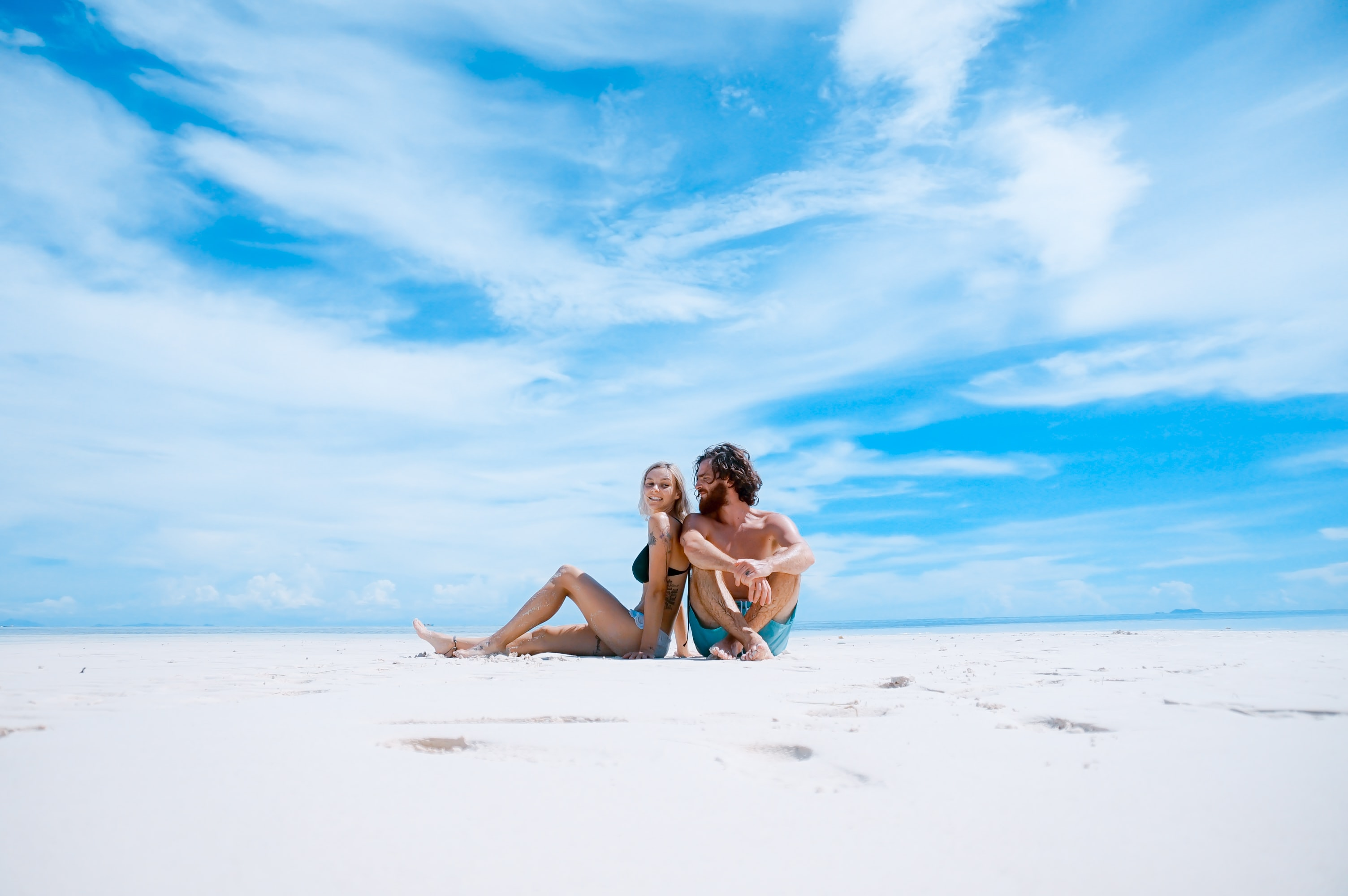 A couple sitting close to each other on a white sandy beach