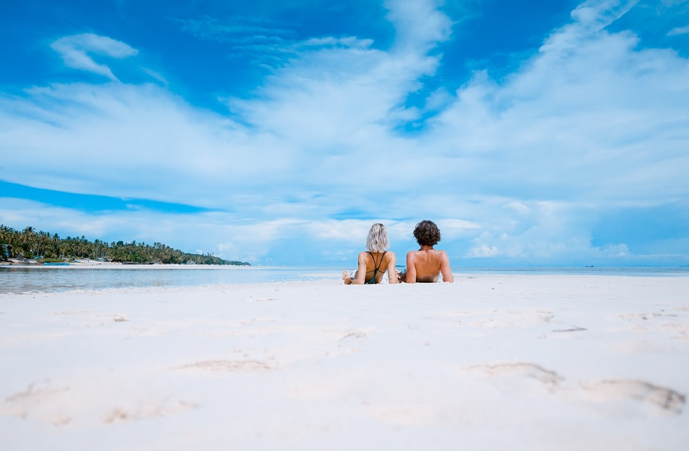 two women lying on white sand facing beach under blue sky