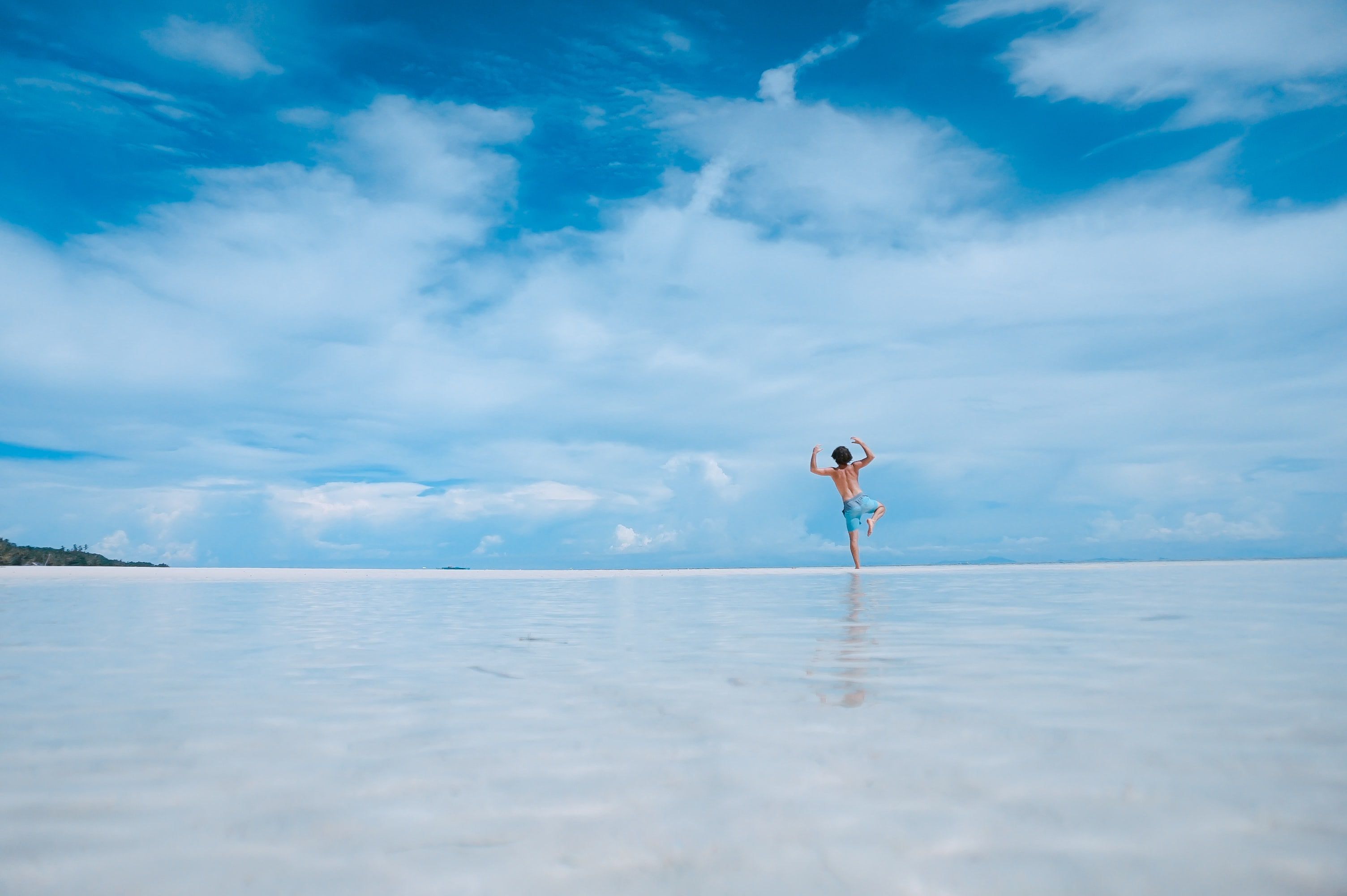 A low shot of a young man standing on one leg and raising his hands on the edge of a beach