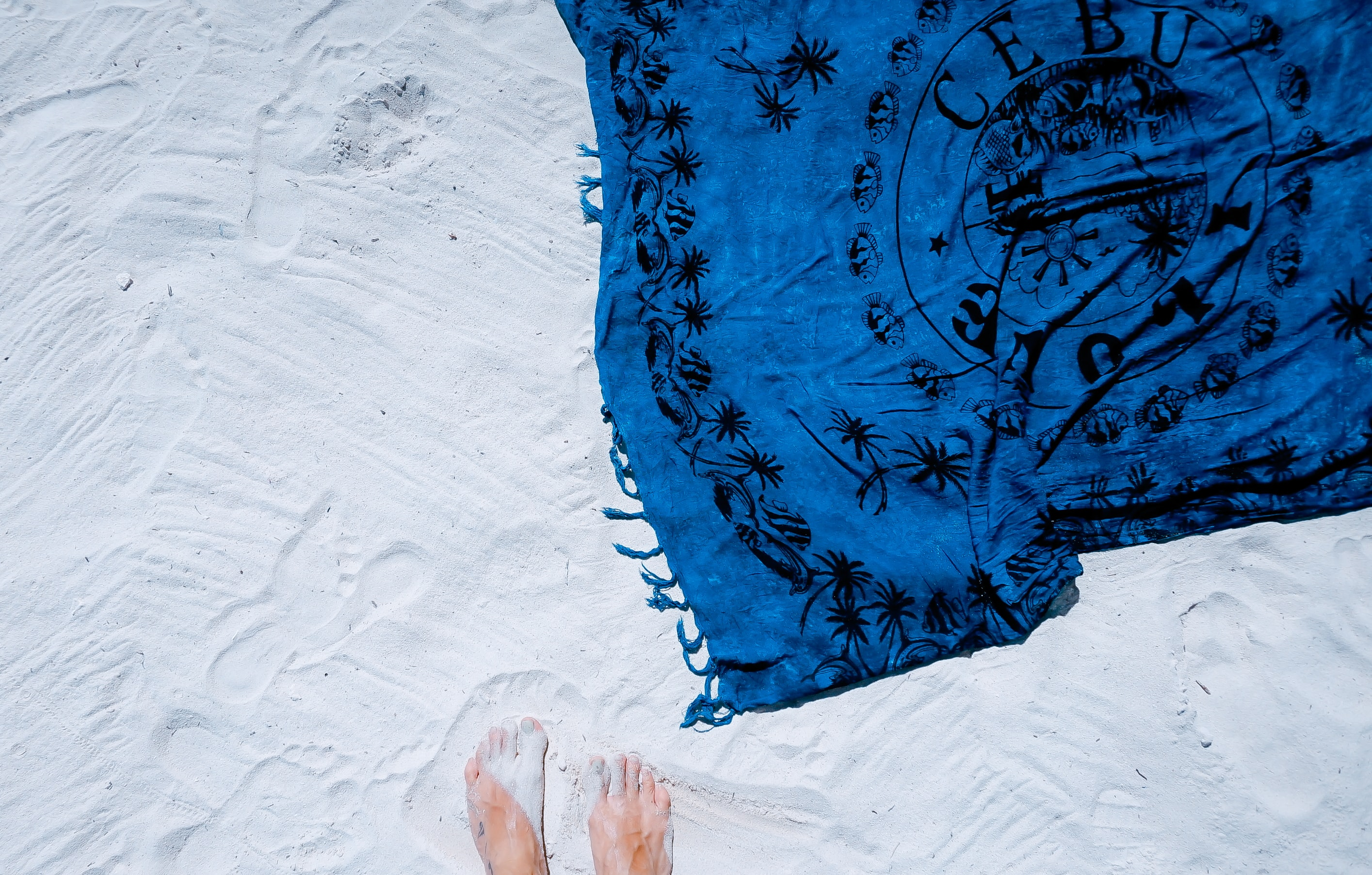 An overhead shot of a person's feet in the white sand next to a blue towel