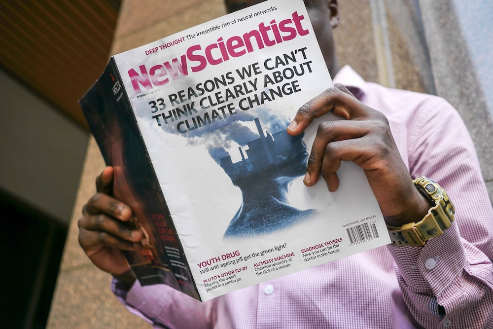 man reading New Scientist book