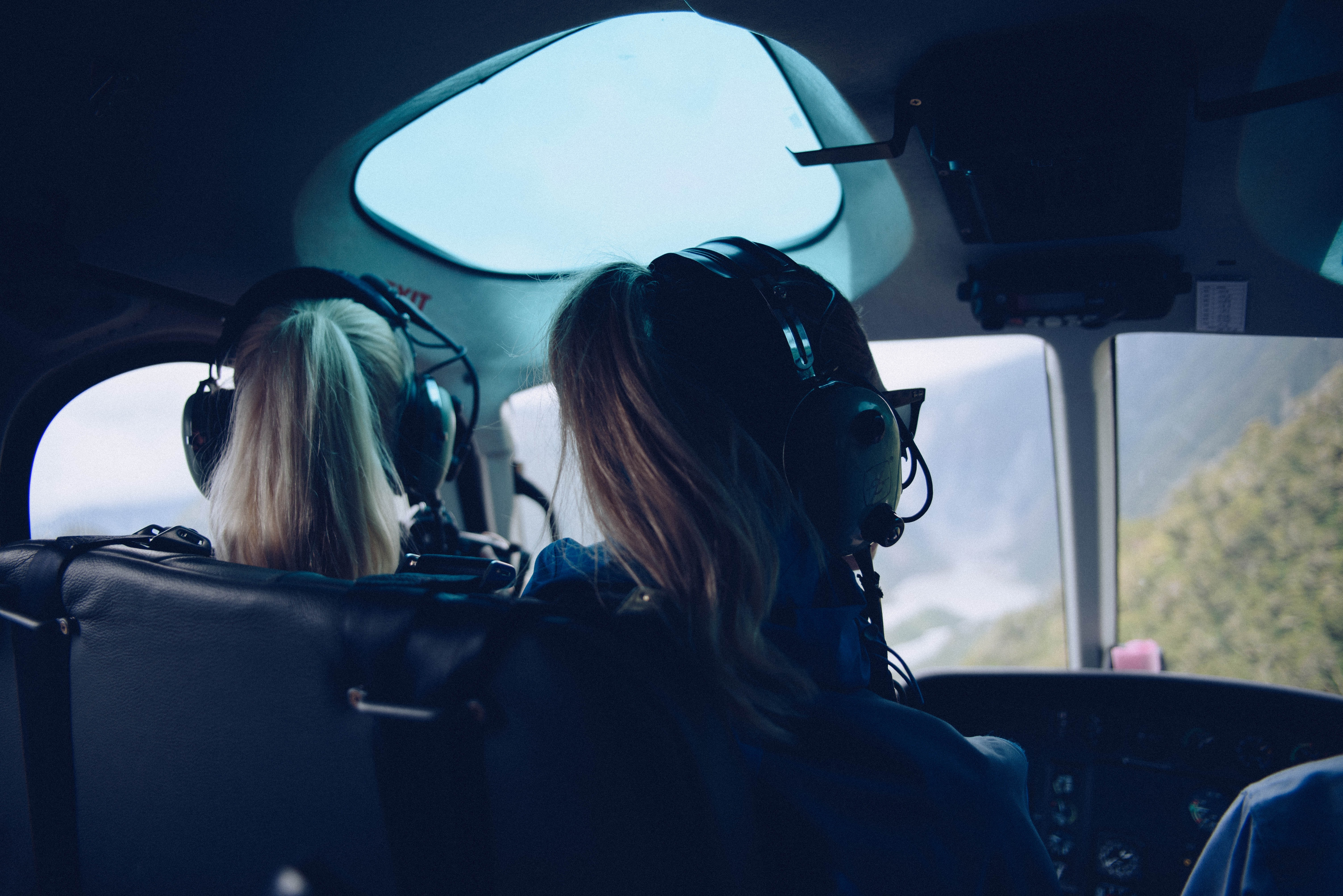 two woman sitting inside helicopter using headphones