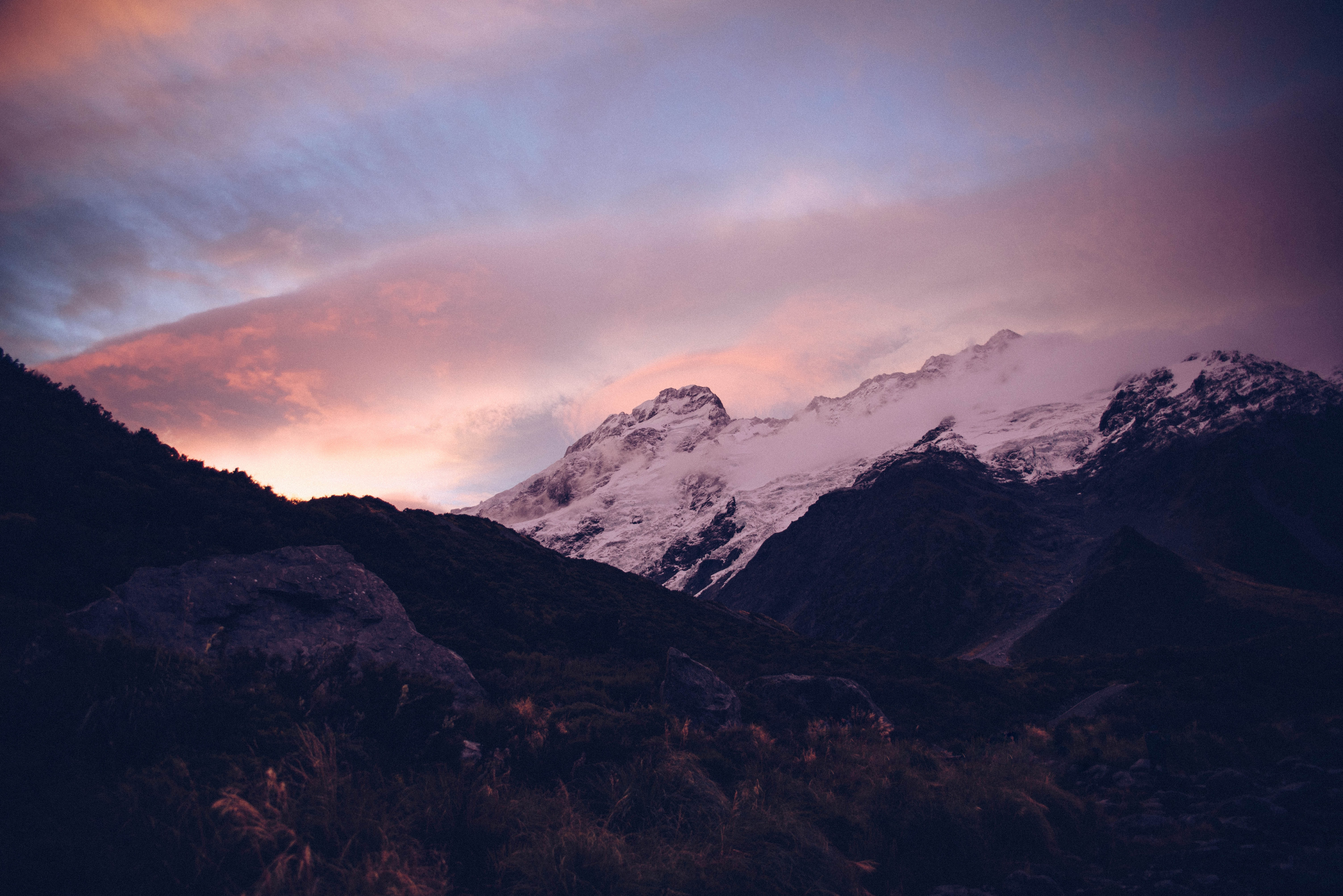 A pink-hued shot of sunset over snowy mountains