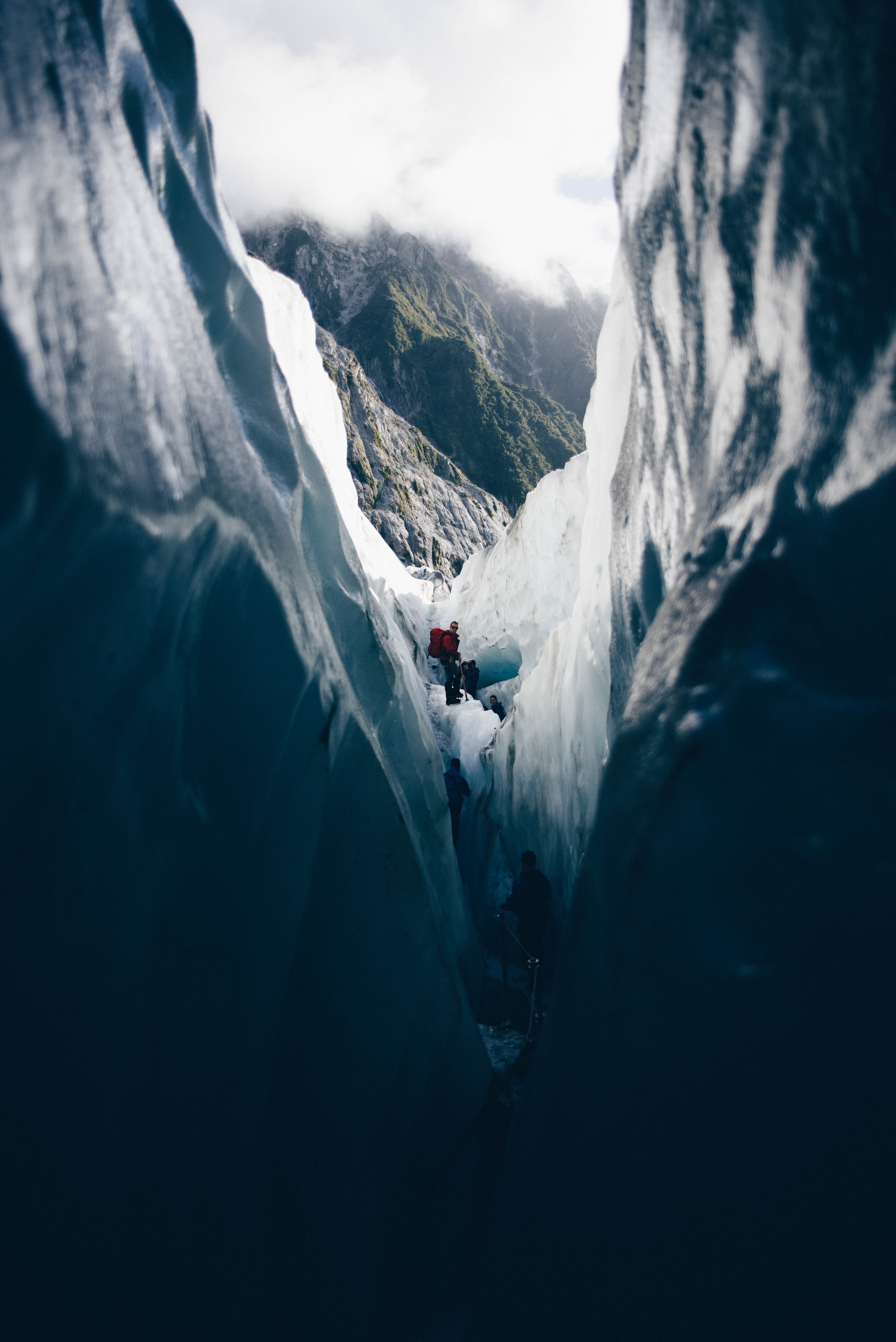 Several hikers exploring a glacial crevasse in the mountains