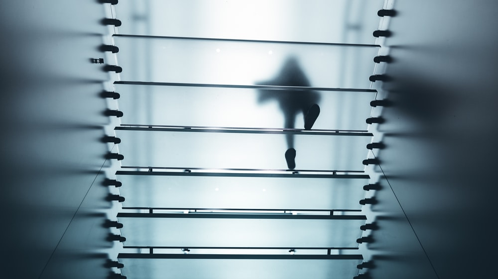 A silhouette of a person walking on translucent glass steps seen from below