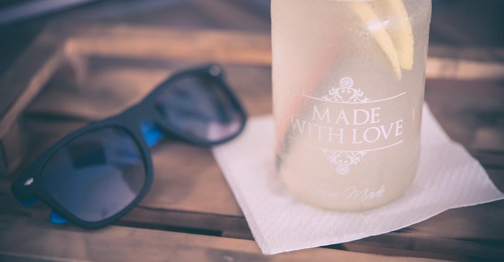 black framed sunglasses beside the glass bottle on table