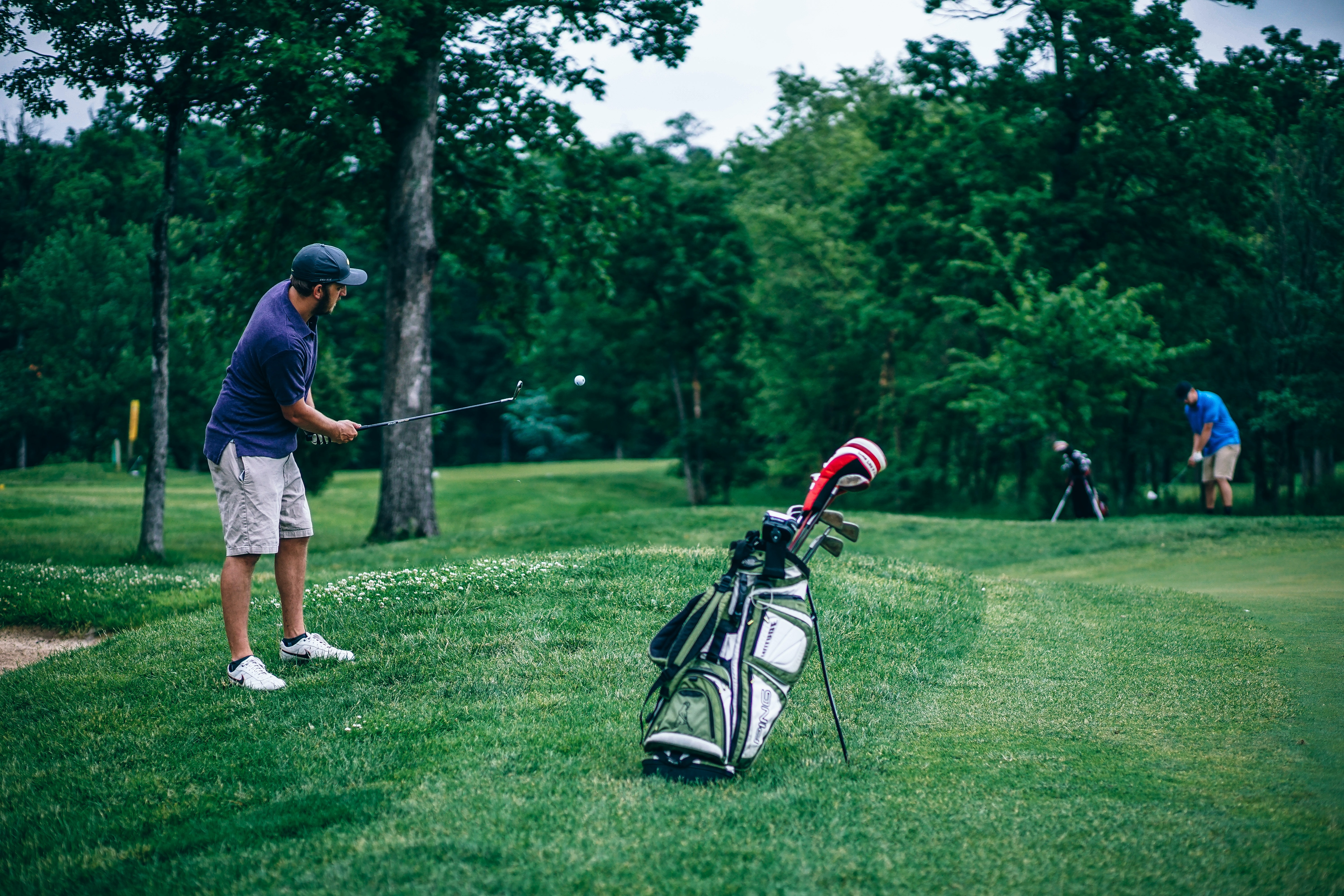 Two men play golf. One has just hit a ball and is watching its trajectory