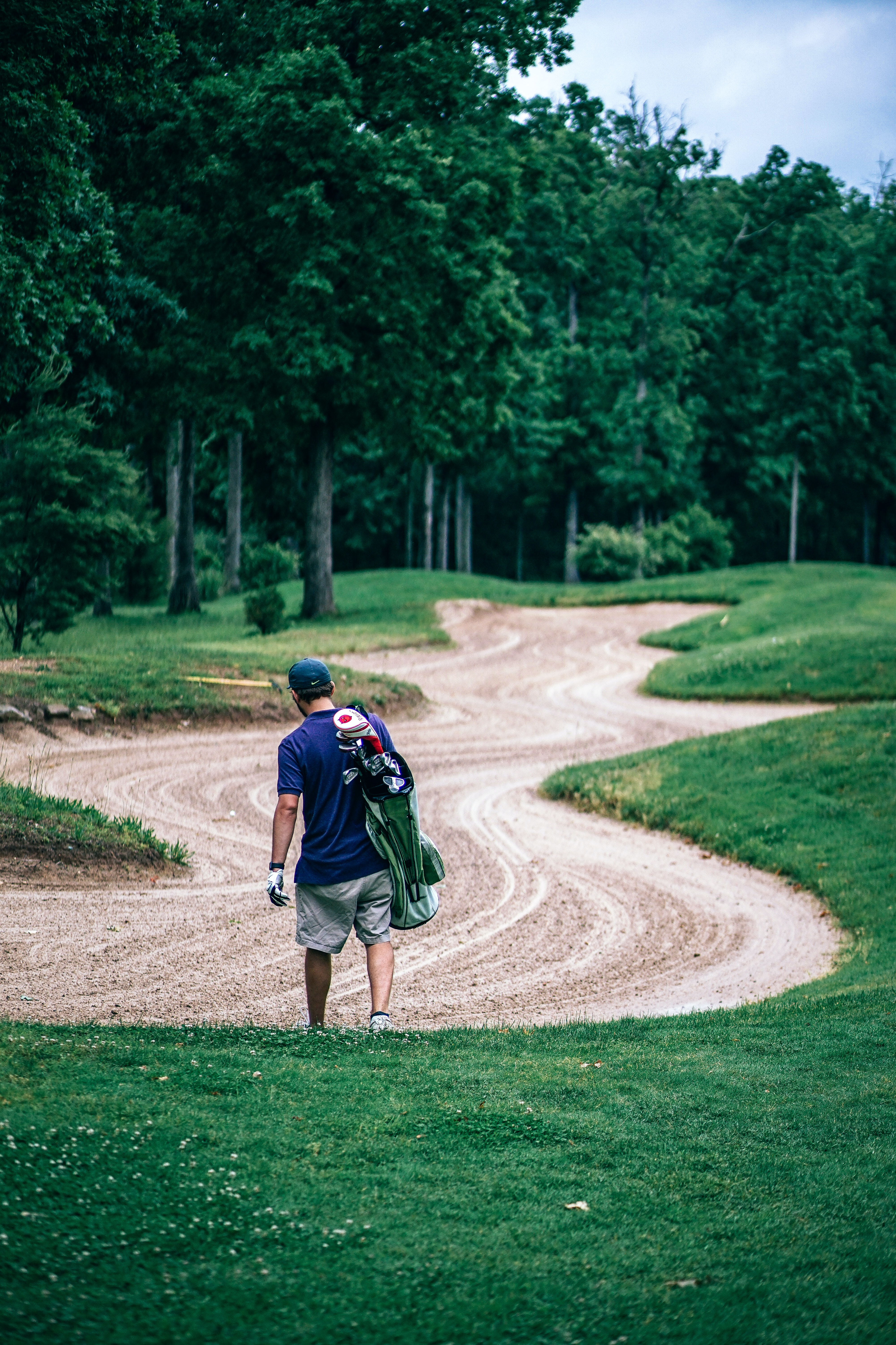 man carrying golf bag along sand zone in golf course