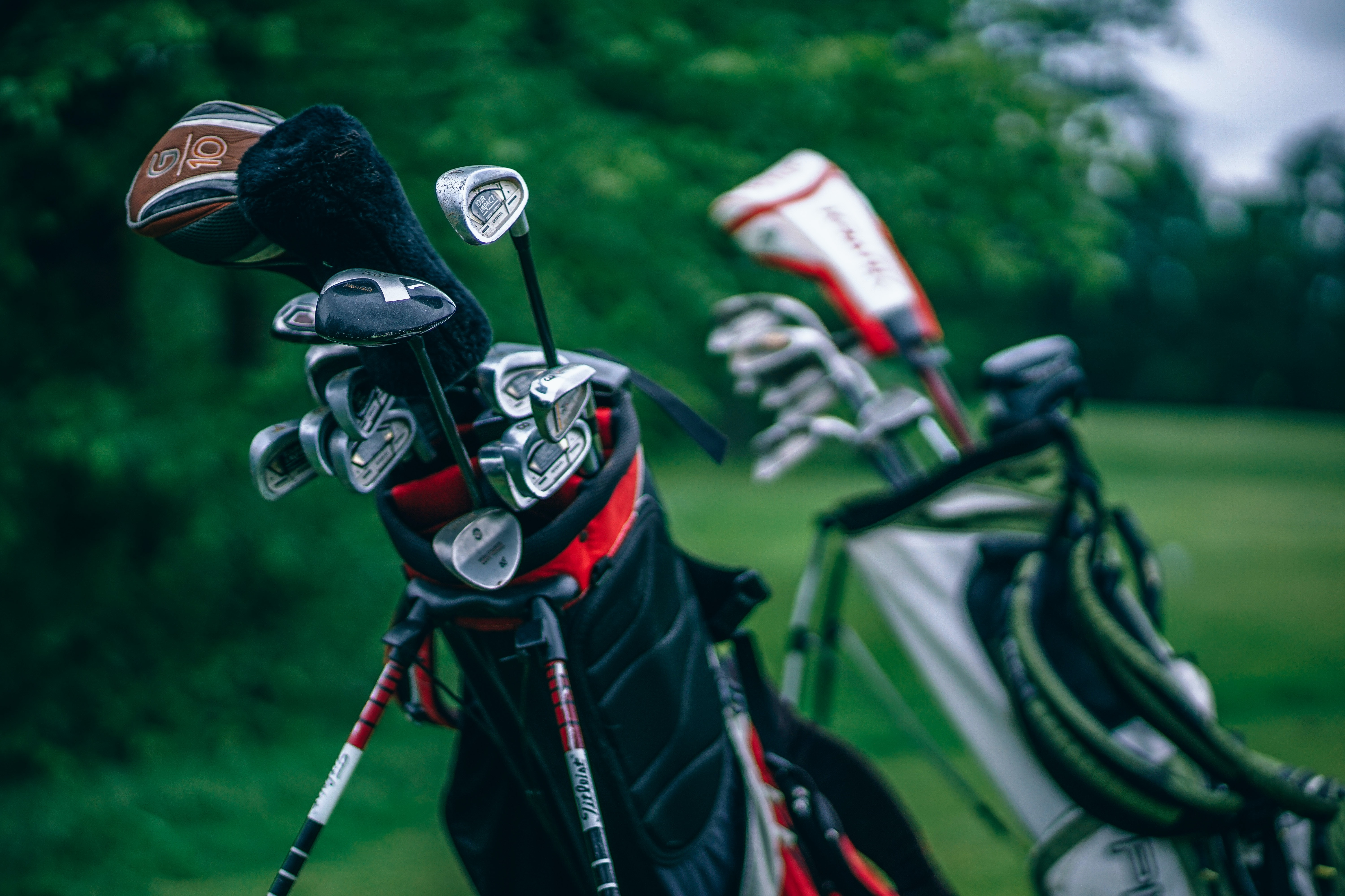 A macro shot of golf club bags sitting off to the side on a real golf course